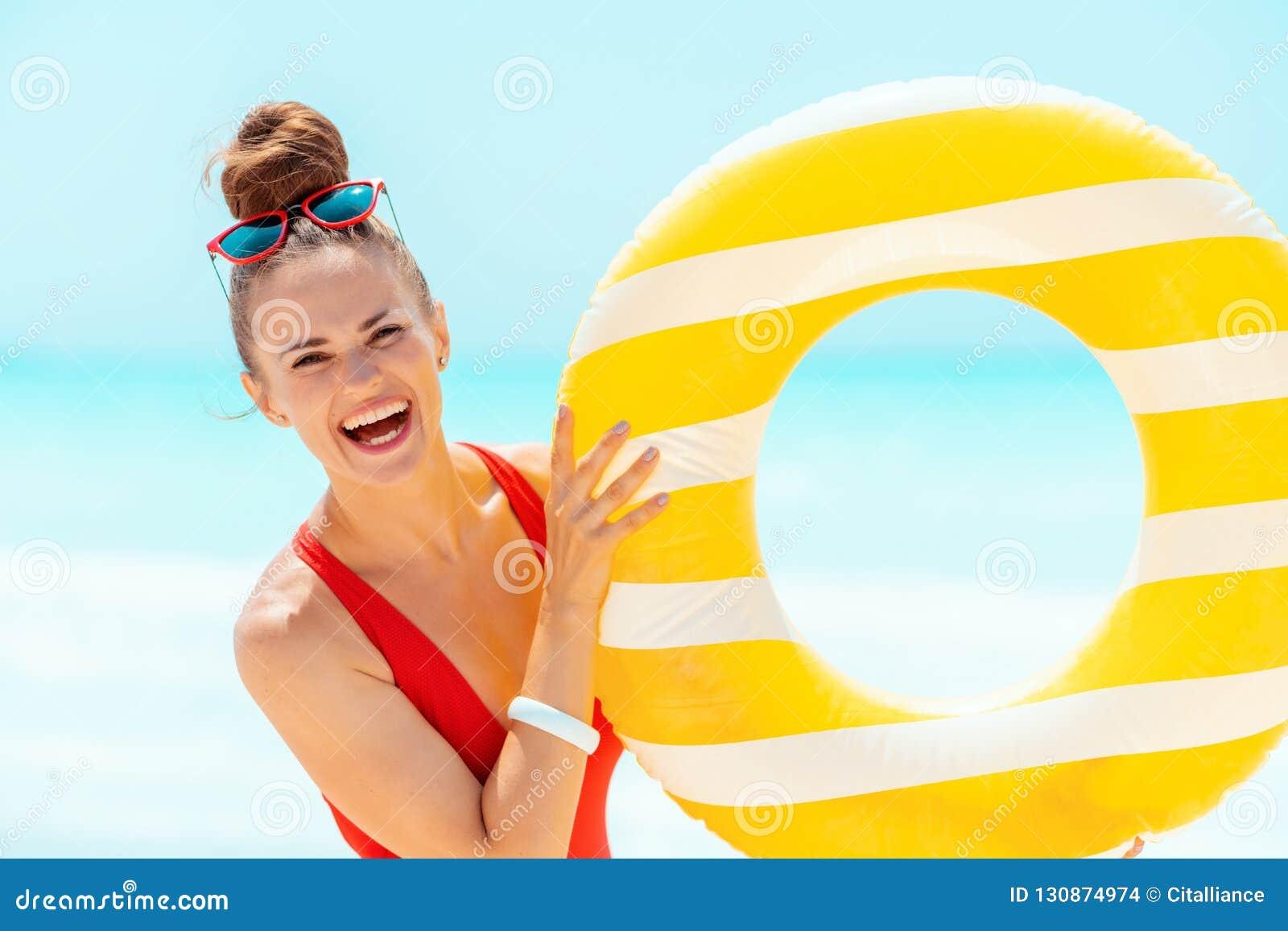 Glimlachende vrouw op zeekust die gele opblaasbare reddingsboei tonen