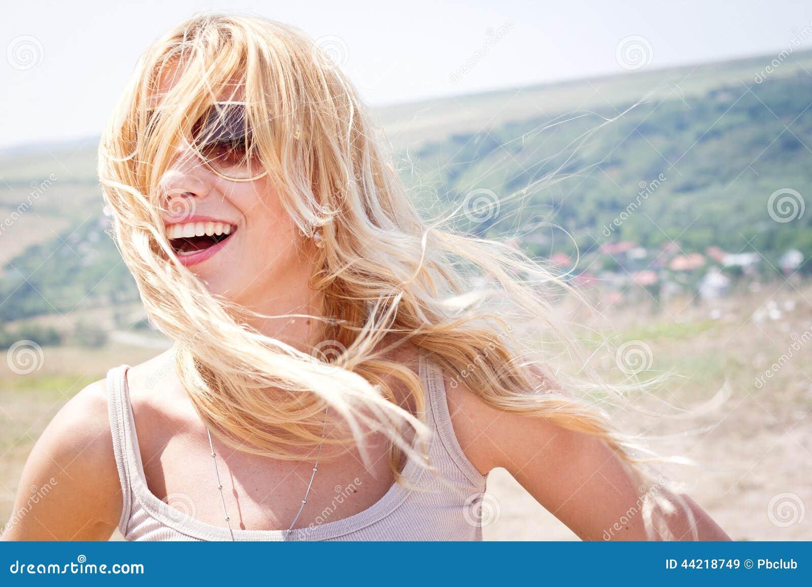 Glimlachende vrouw in openlucht met wind geblazen haar