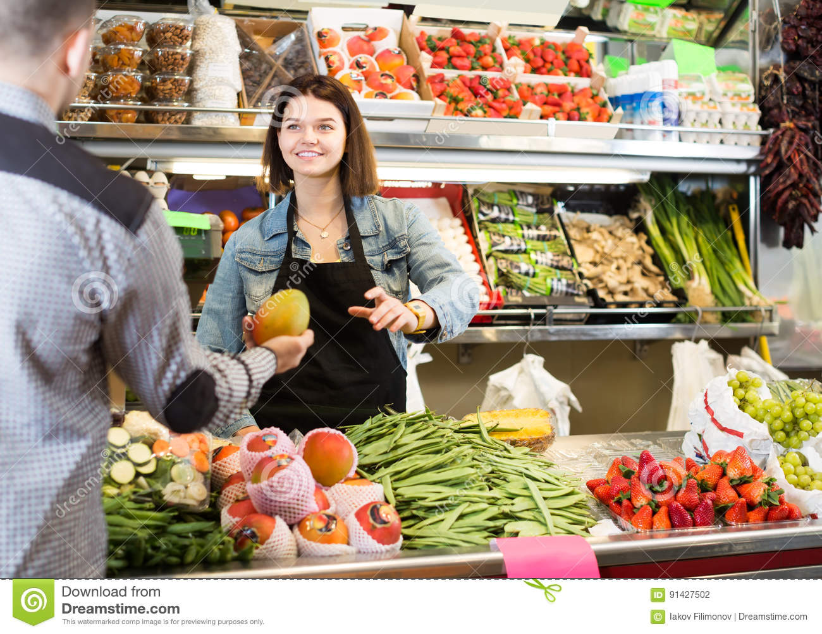 bd573a0cc4a27d De glimlachende vrouwelijke verkopers bijwonende klant om vers fruit te  kopen en de groenten in kruidenierswinkel winkelen