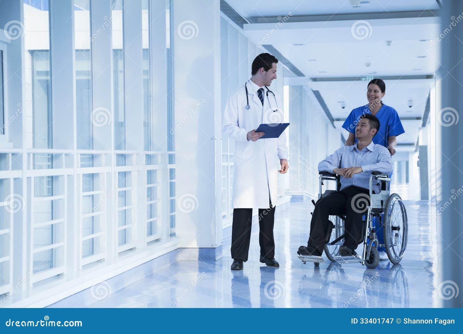 Glimlachende vrouwelijke verpleegsters duwende en bijwonende patiënt in een rolstoel in het ziekenhuis, die aan arts spreken