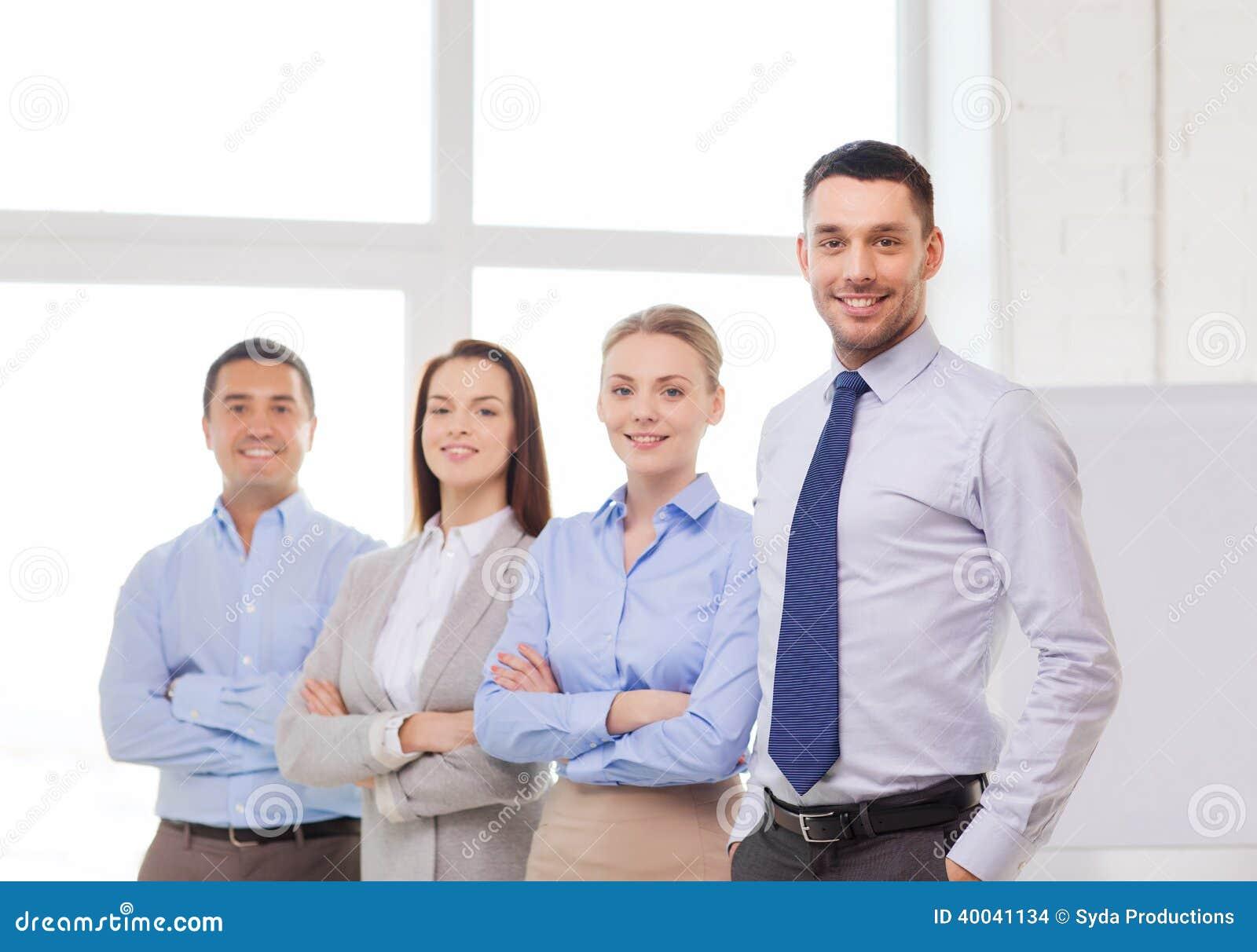 Glimlachende zakenman in bureau met team op rug