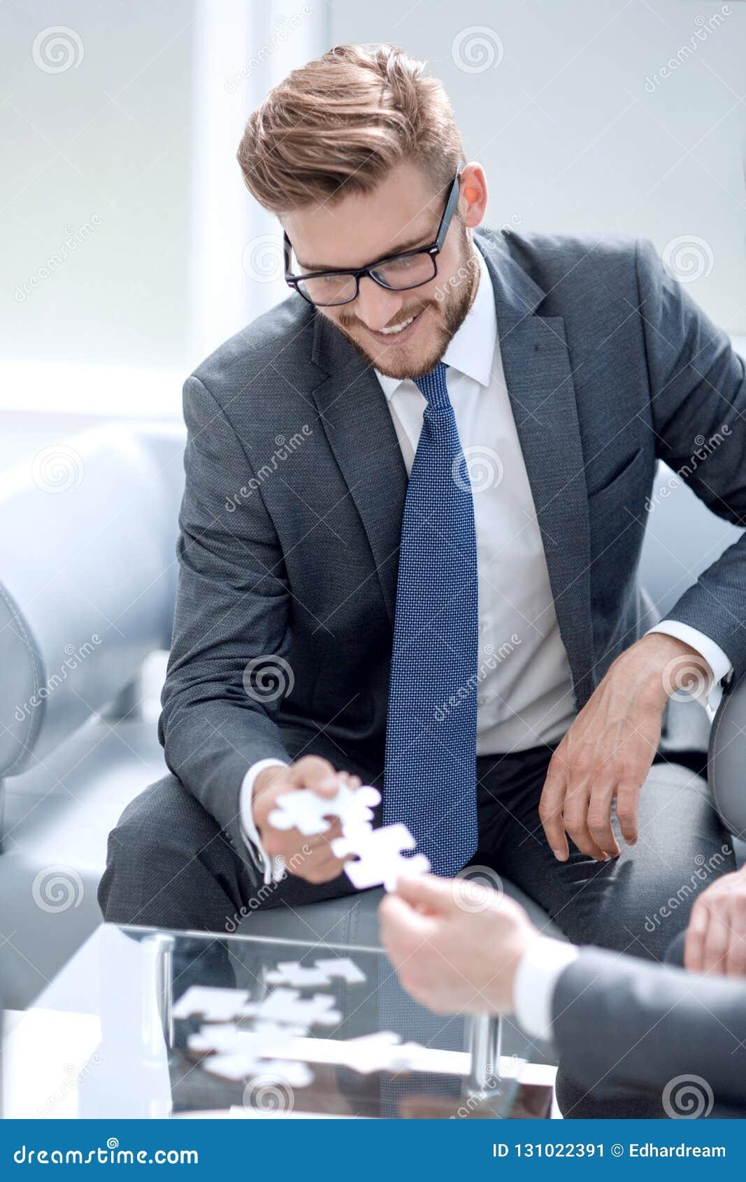 Glimlachende zakenman die de partner helpen om het raadsel te voltooien