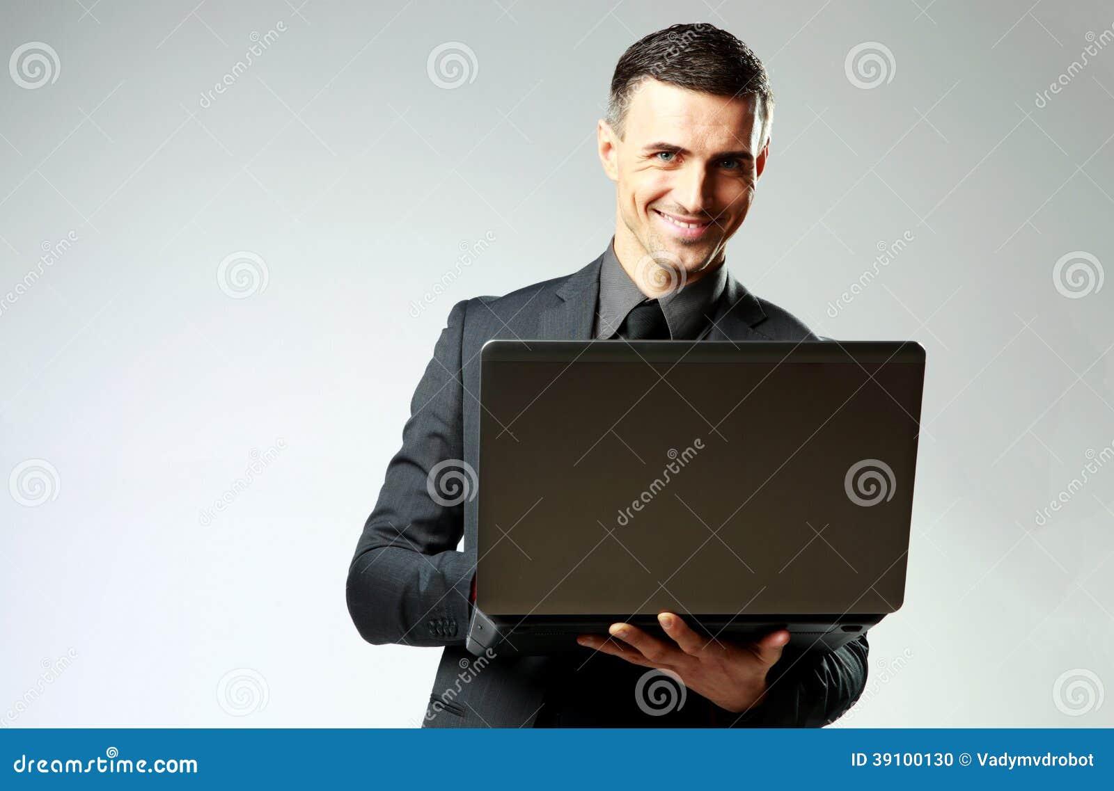 Glimlachende zakenman die laptop met behulp van