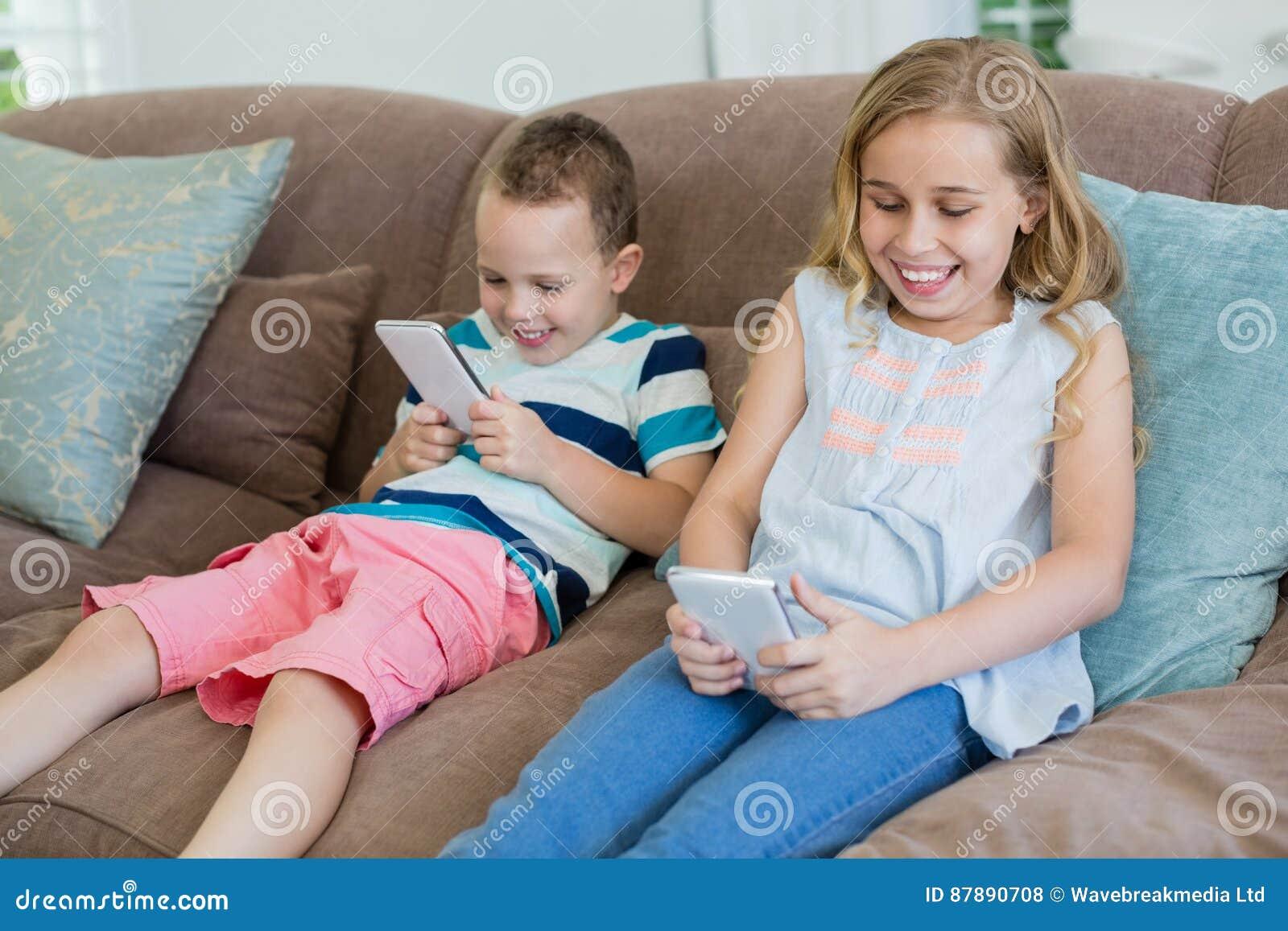 Glimlachende zuster en broerzitting op laag die mobiele telefoon in woonkamer met behulp van