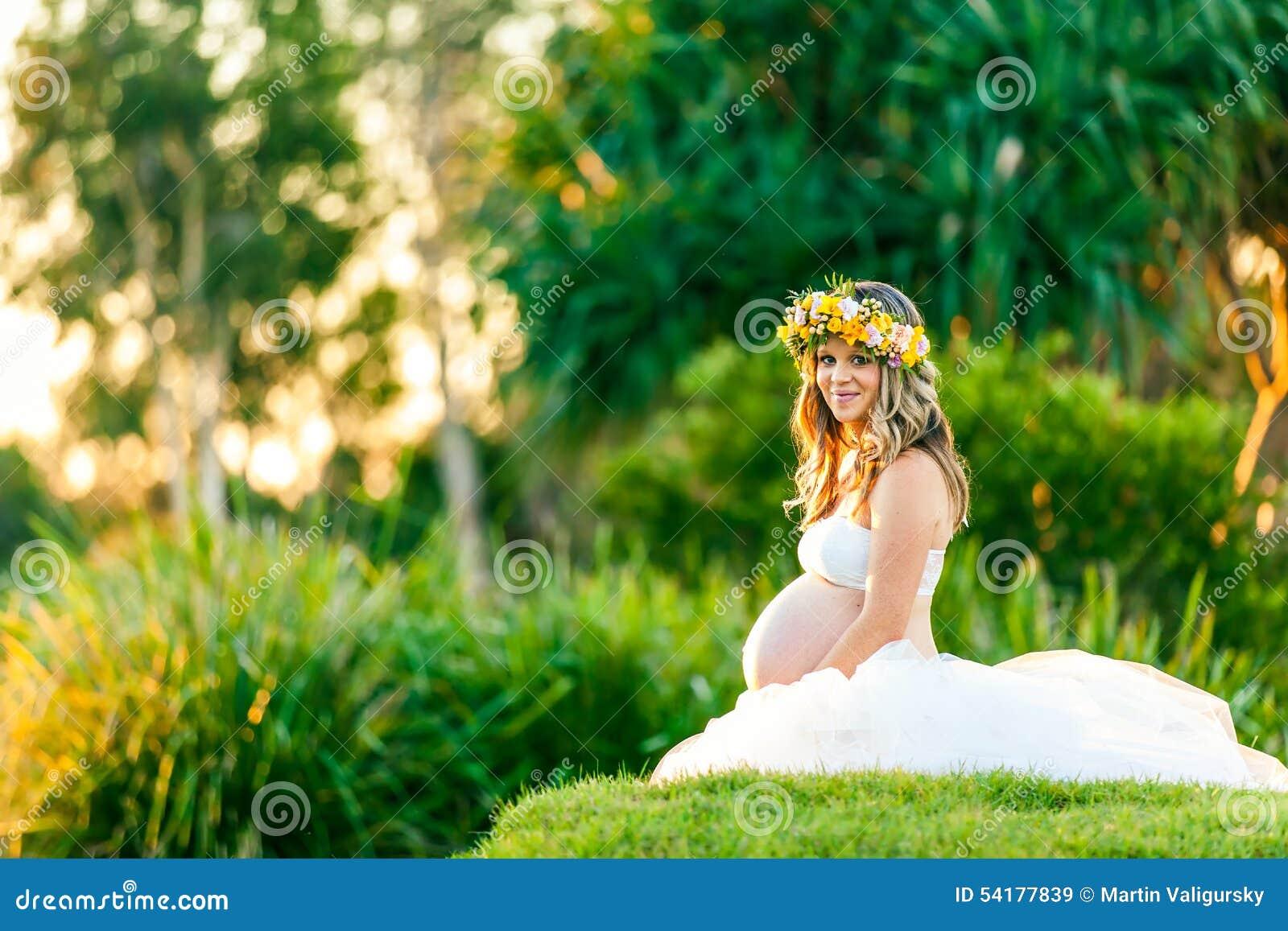 Glimlachende zwangere vrouw in witte kleding met bloemen in haar haar