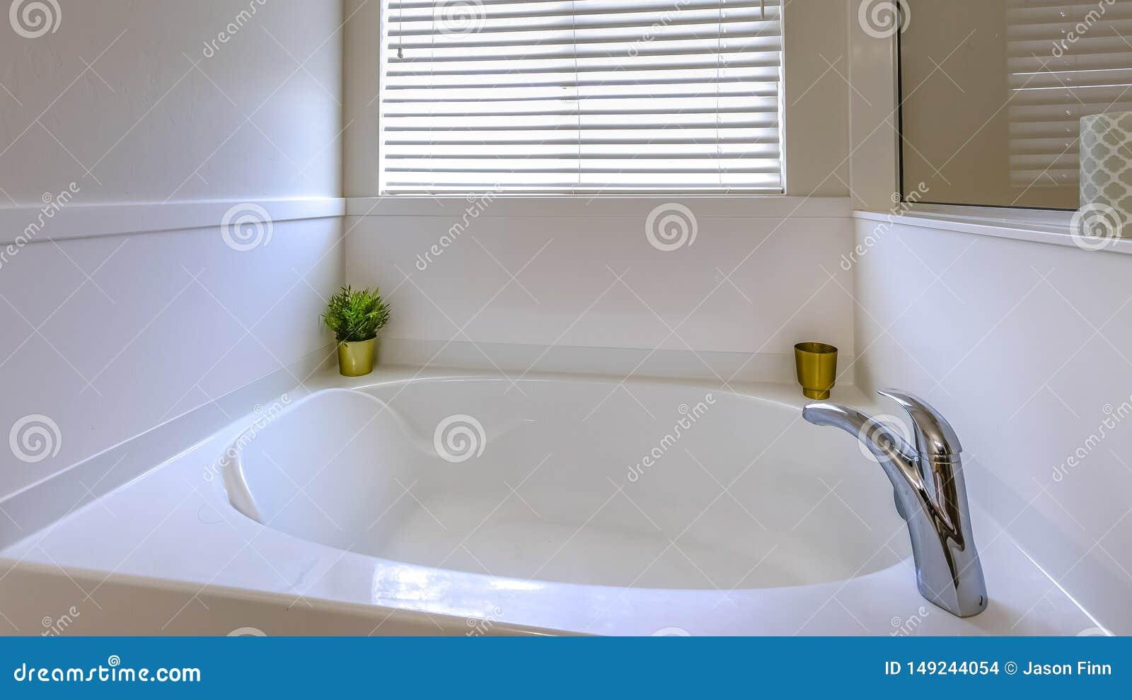 Glimma vitt badkar för panoramaram inom ett badrum med en stor spegel på väggen