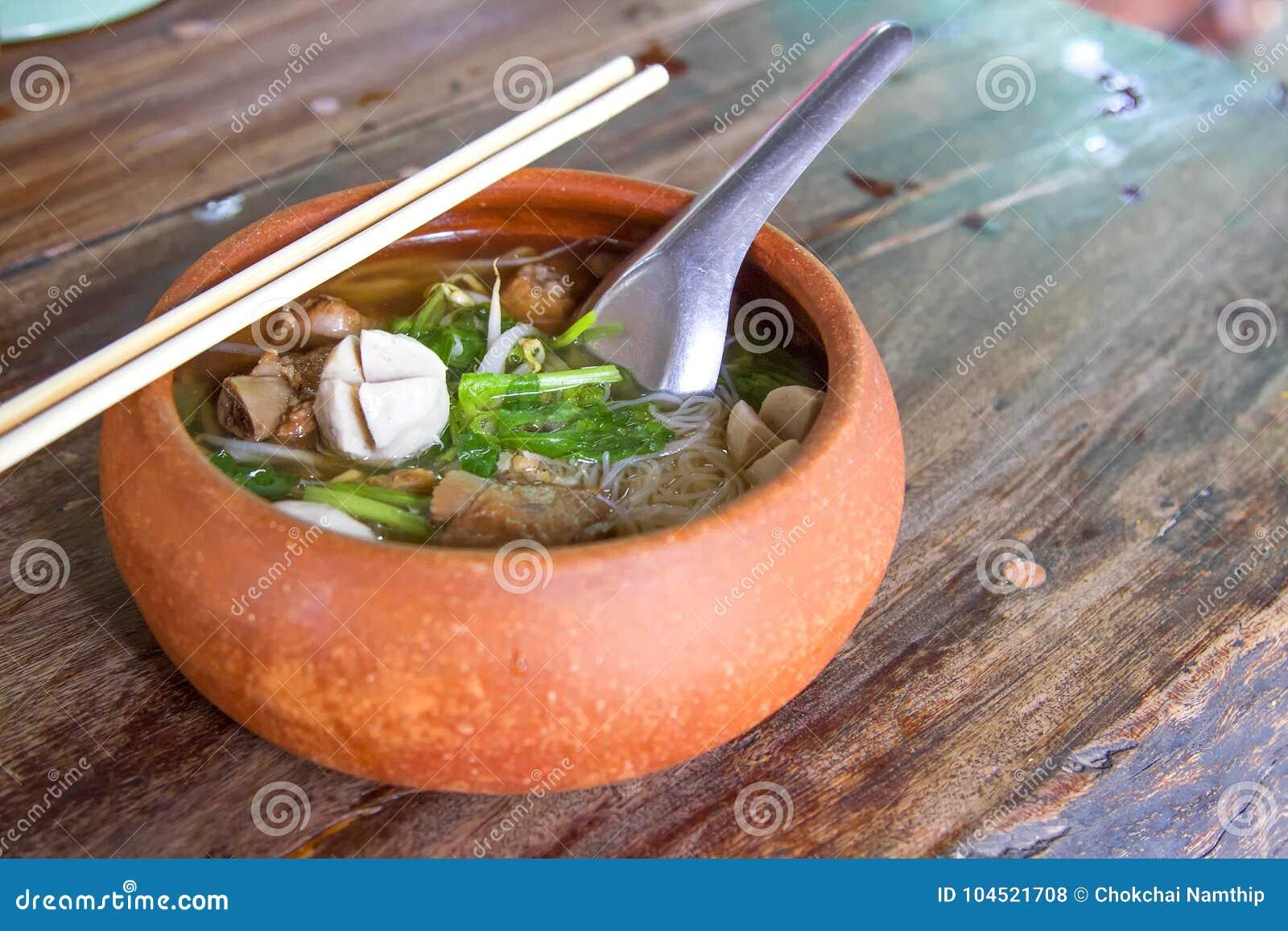 Glinianego garnka ryżowi kluski stawiają dalej drewnianego stół