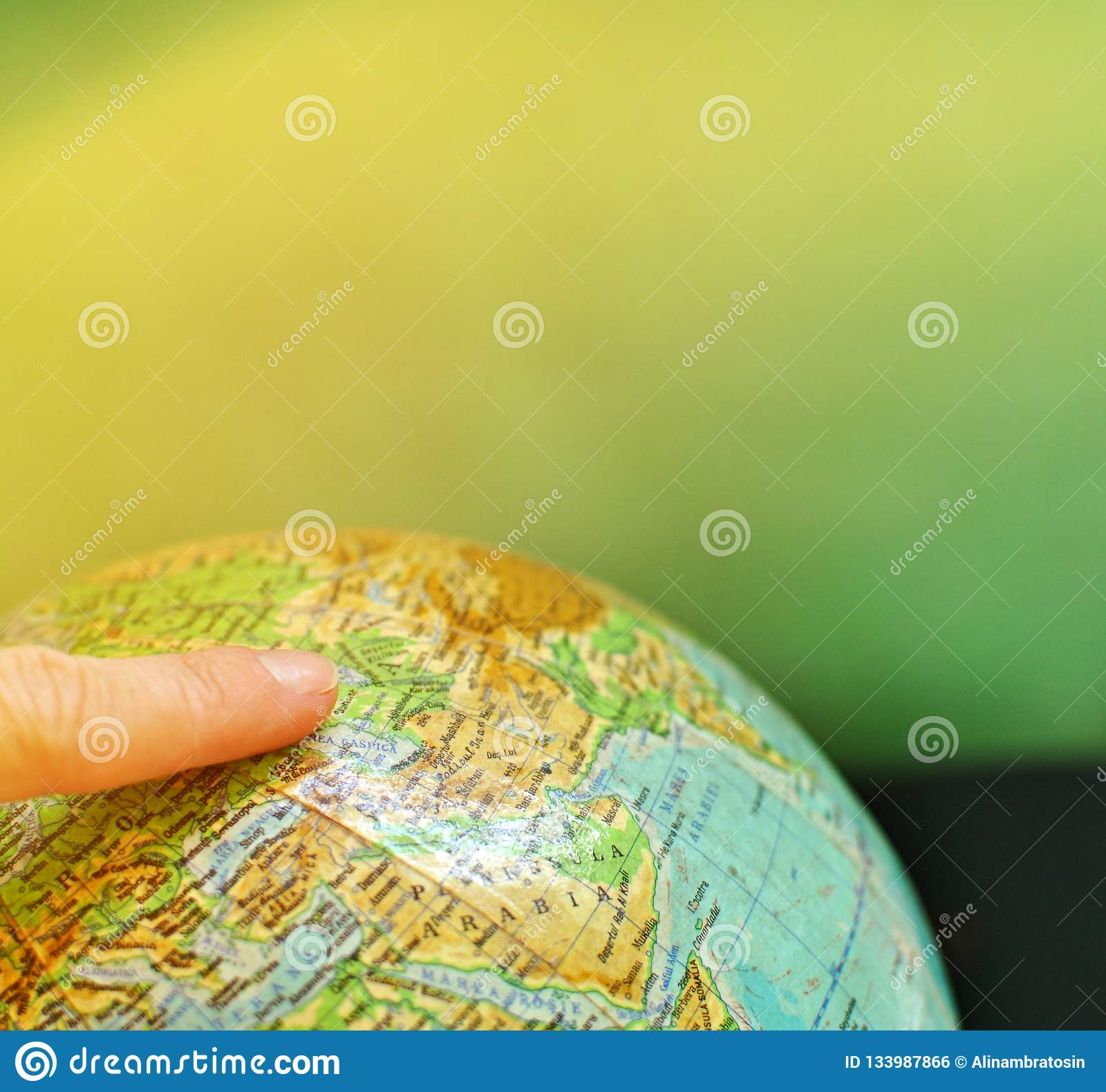 A globe world map with an index finger on it