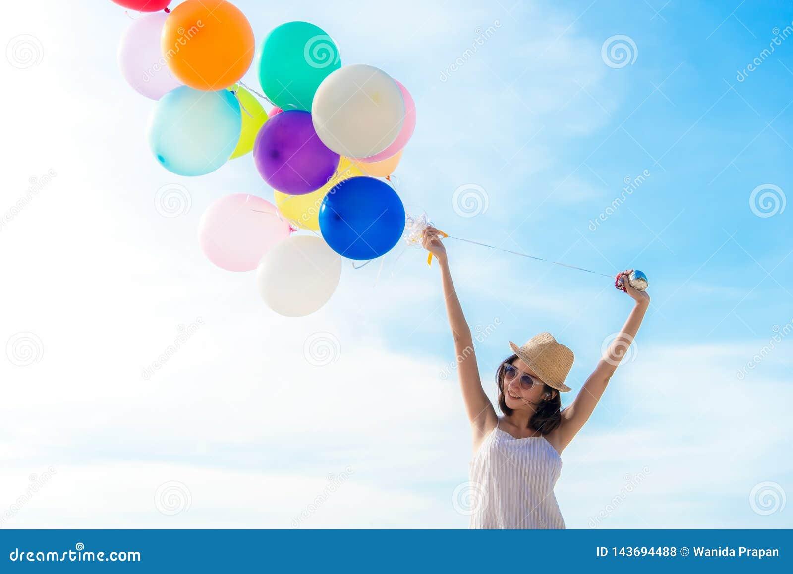 Globo asiático sonriente de la tenencia de la mano de la frialdad de la mujer de la forma de vida en la playa Relájese y goce en