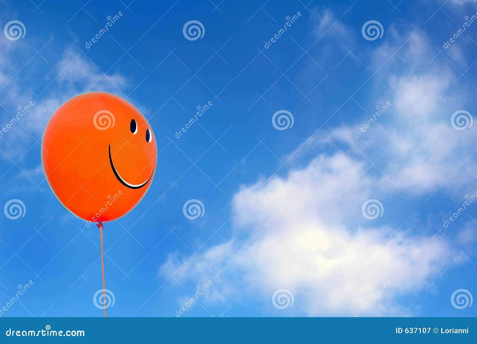 Globo feliz rojo de la cara con el fondo del athe del cielo azul