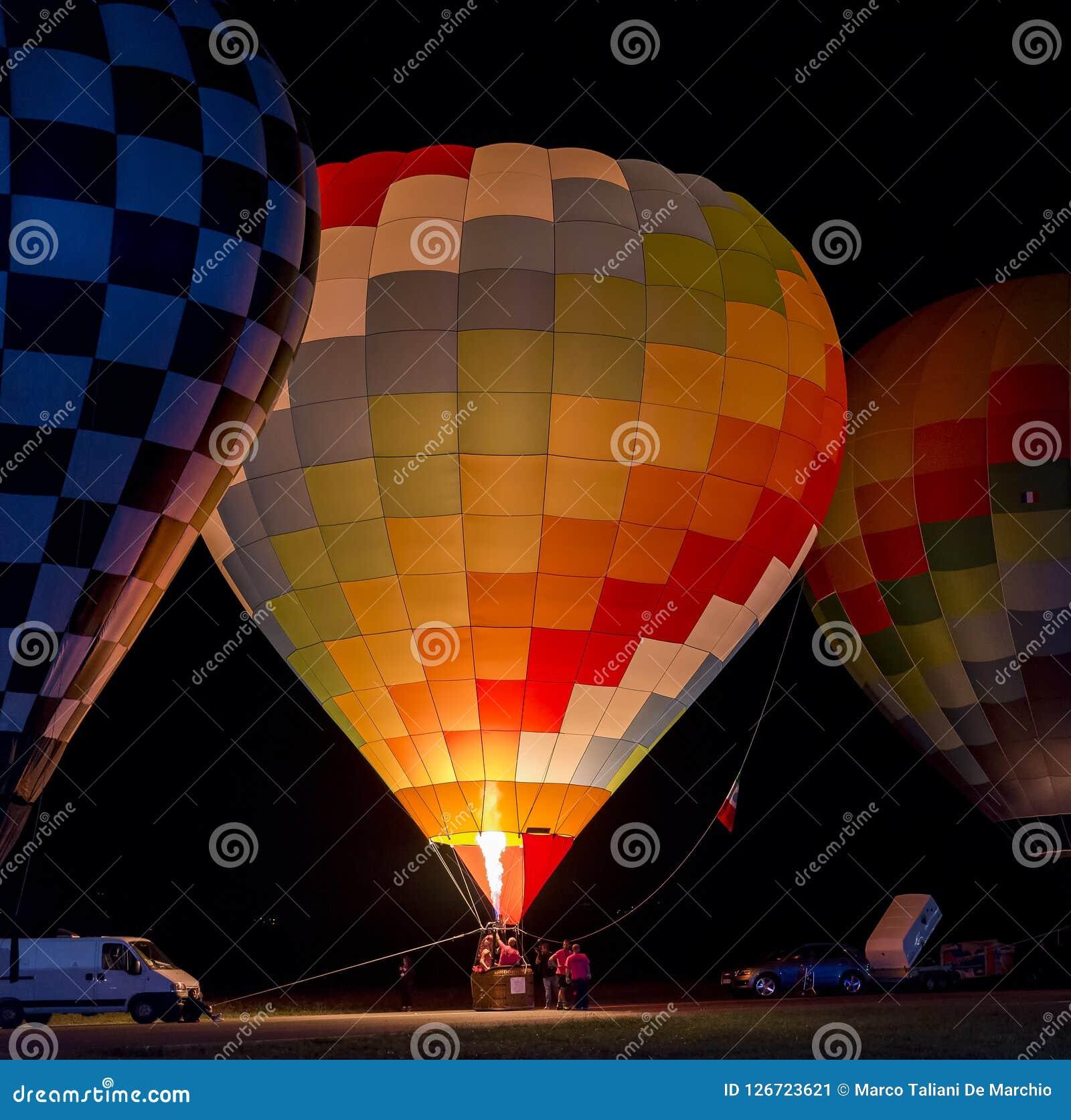 Globo hermoso y colorido del aire caliente listo para el despegue en la noche