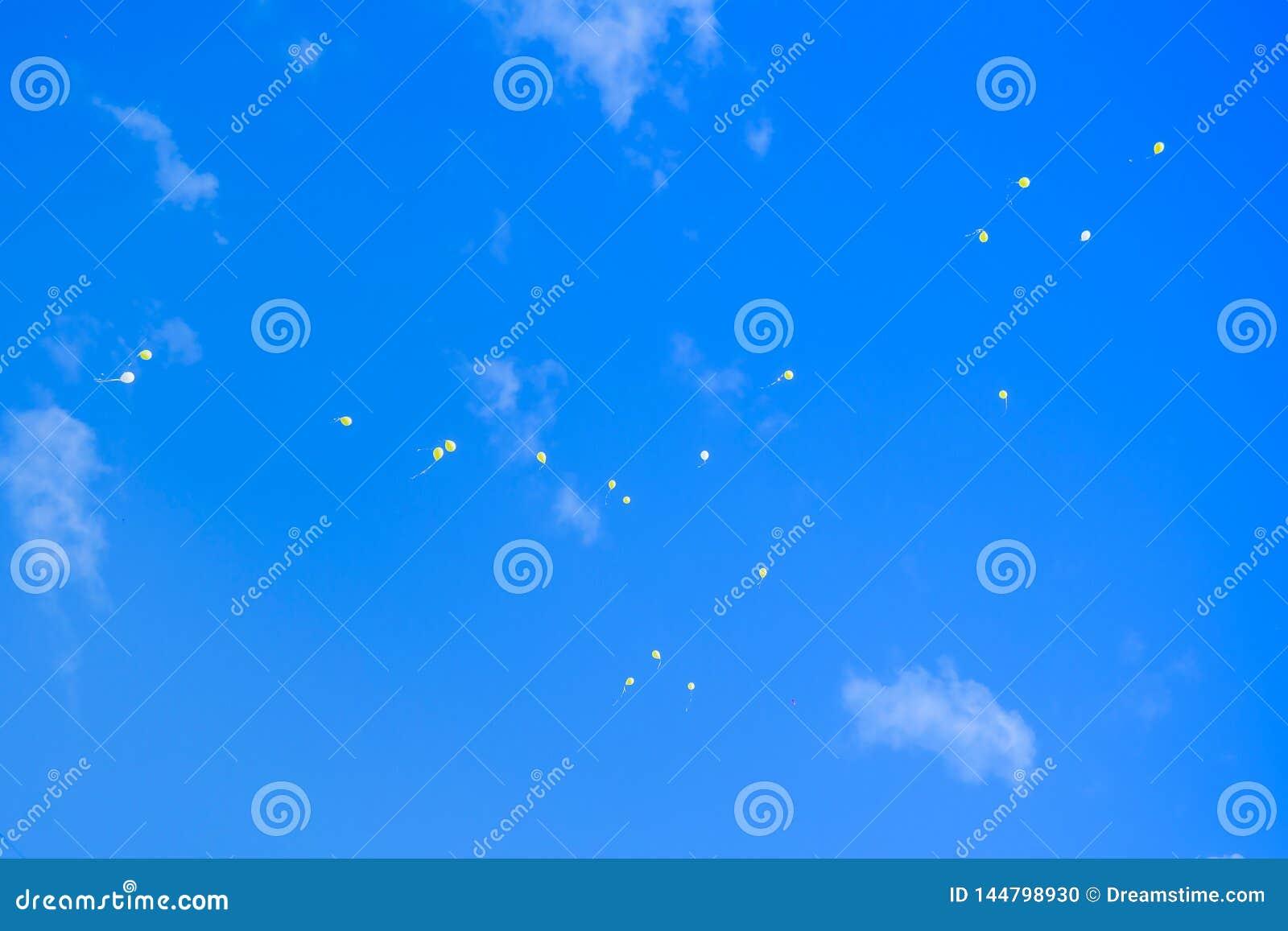 Globos coloridos del helio en vuelo contra el cielo azul, saludos del cumpleaños