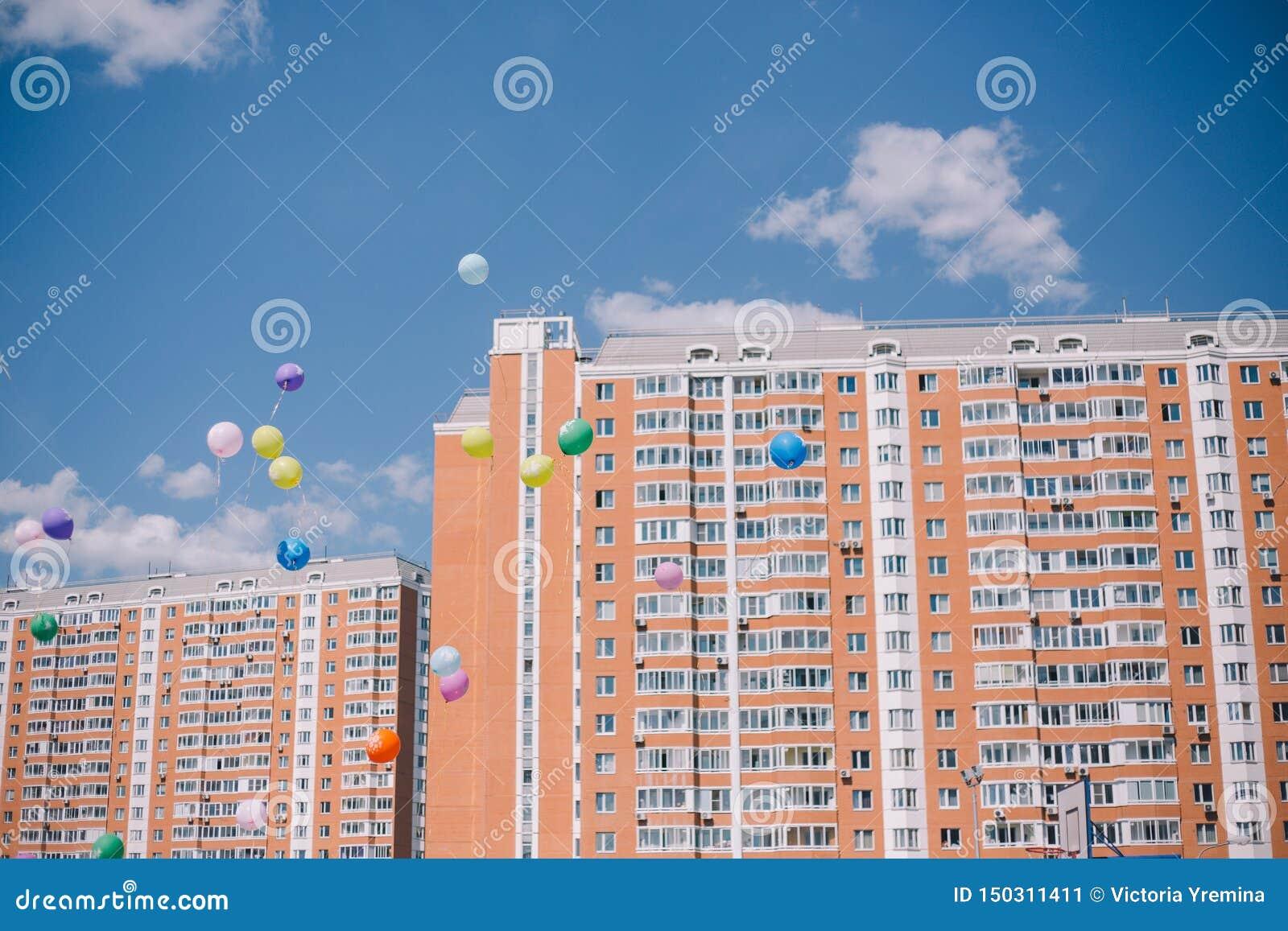 Globos contra el cielo azul, las nubes y los edificios residenciales Última llamada y graduación en la escuela