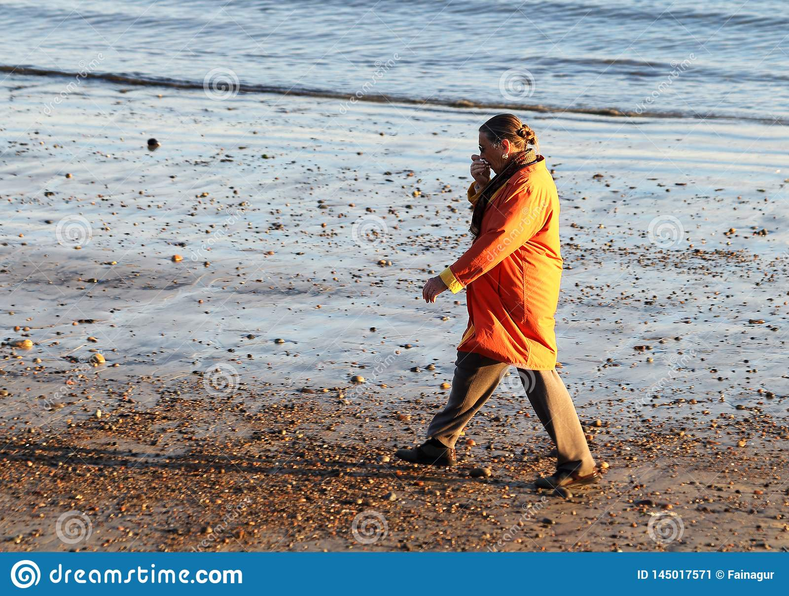 A woman in the orange coat walking on the beach at early spring in Gloucester, Massachusetts