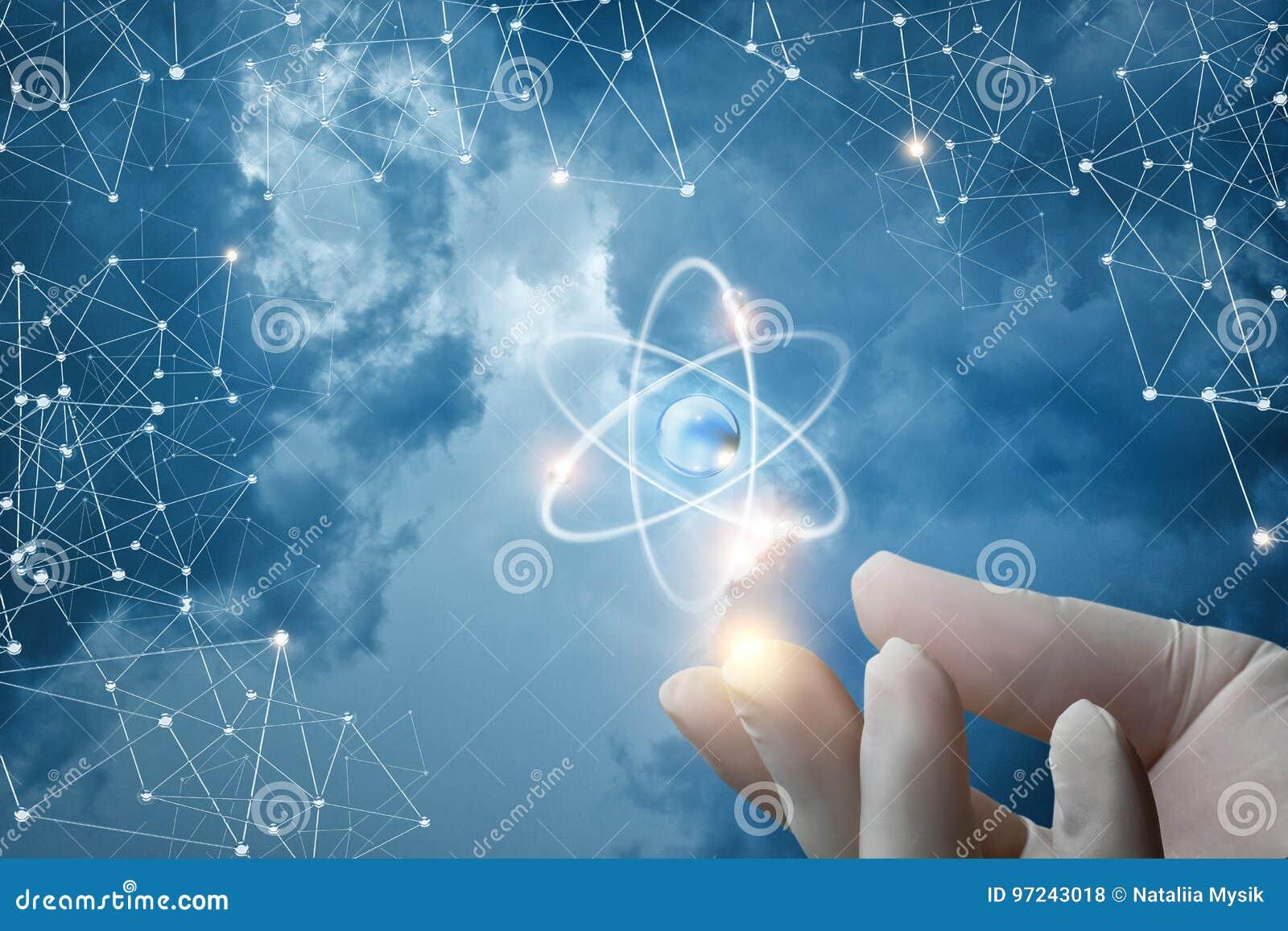 Gloved ręka pokazuje atom