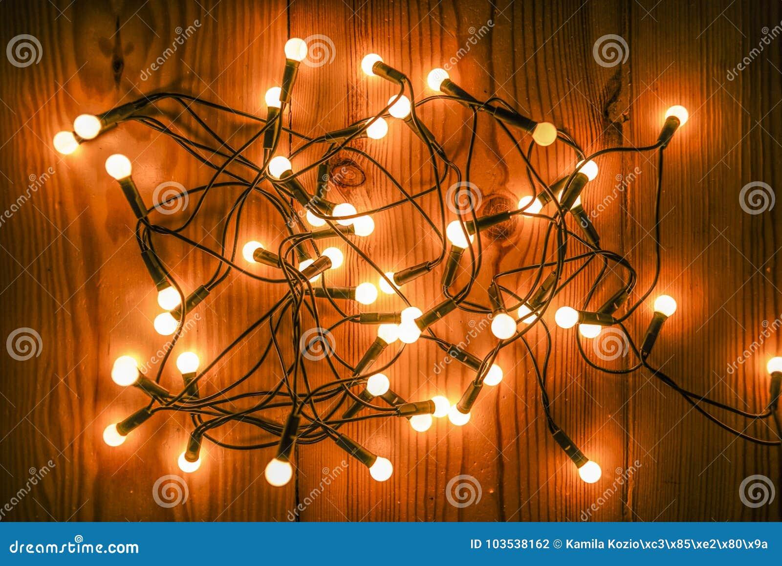 Glowing Christmas tree lights lying on a wooden floor