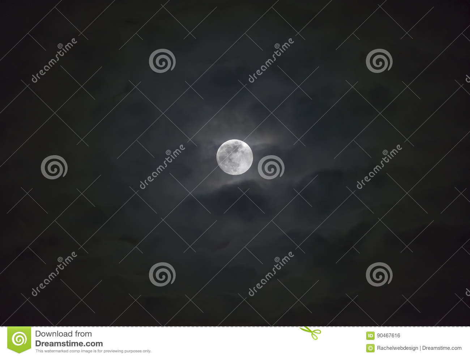 Glowing full moon behind wispy layers of moody clouds, atmospheric night sky scene