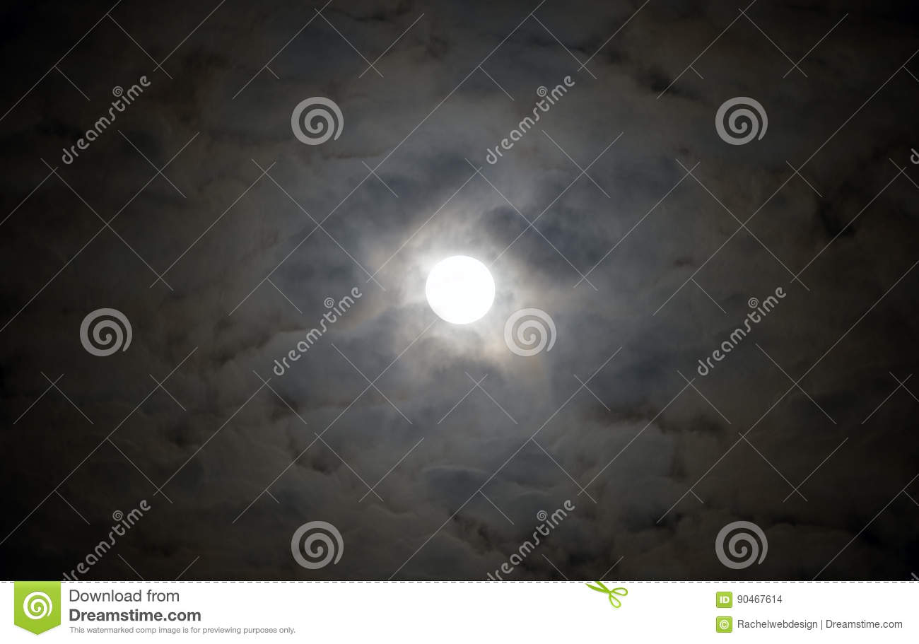 Glowing full moon surrounded by circle of moody alien clouds lit