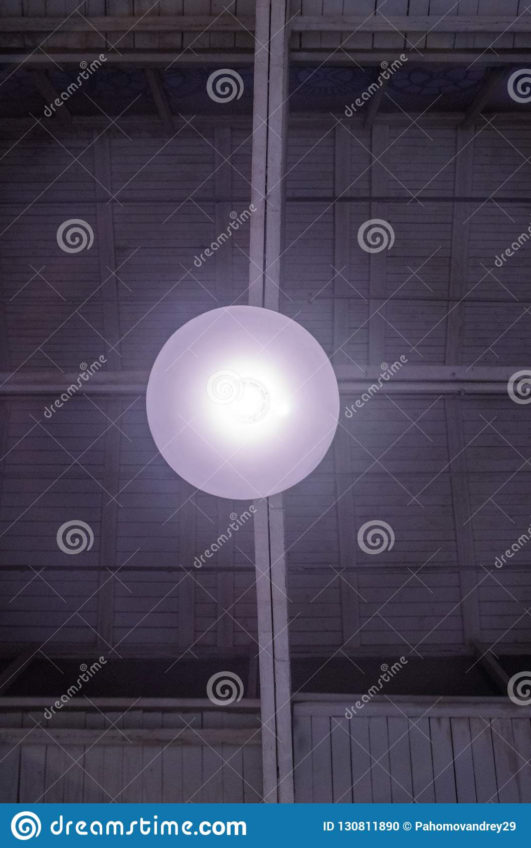 Glowing garage lamp under the ceiling. gray white colors