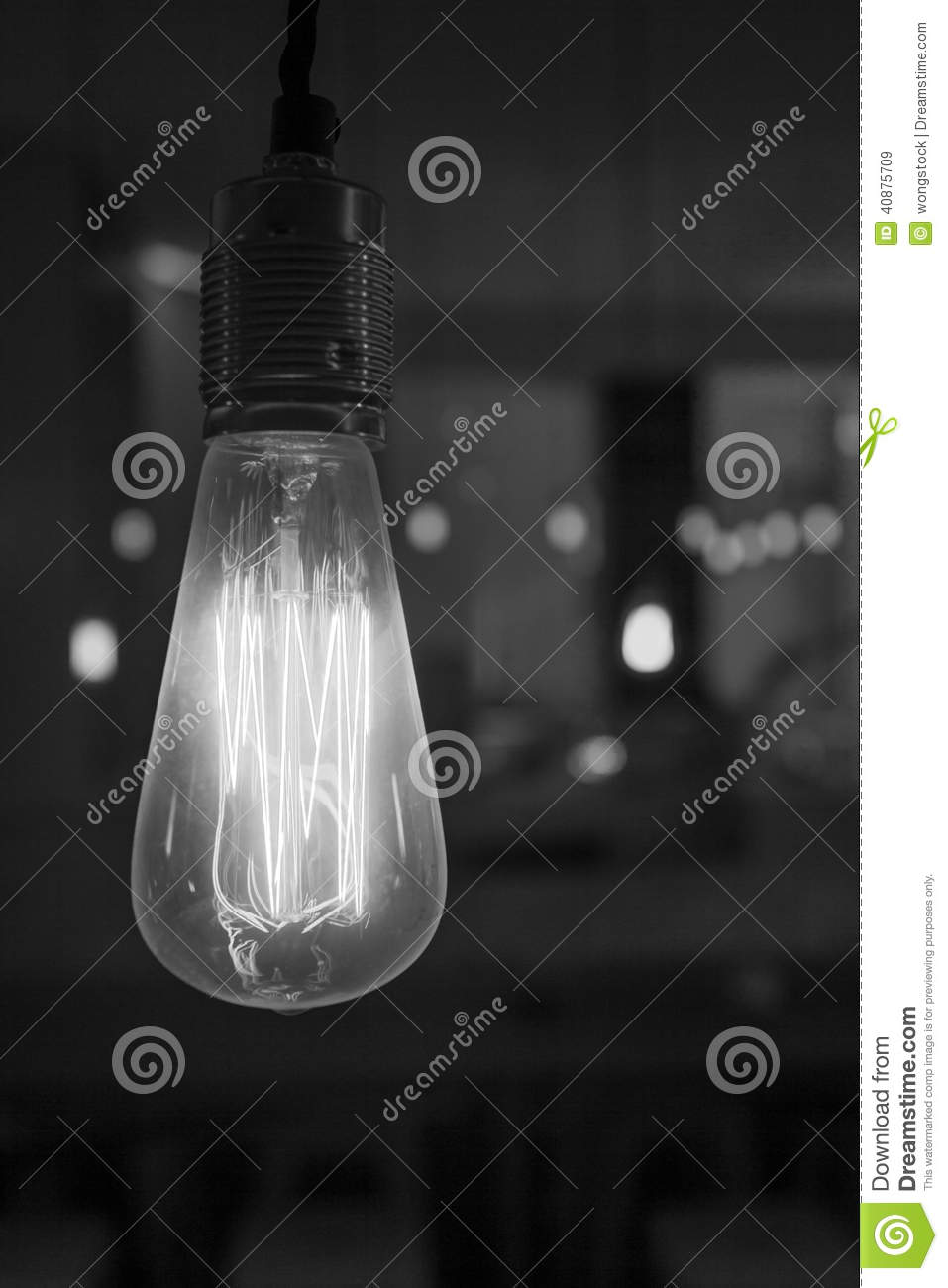 Glowing lightbulb dangling from the ceiling in black and white