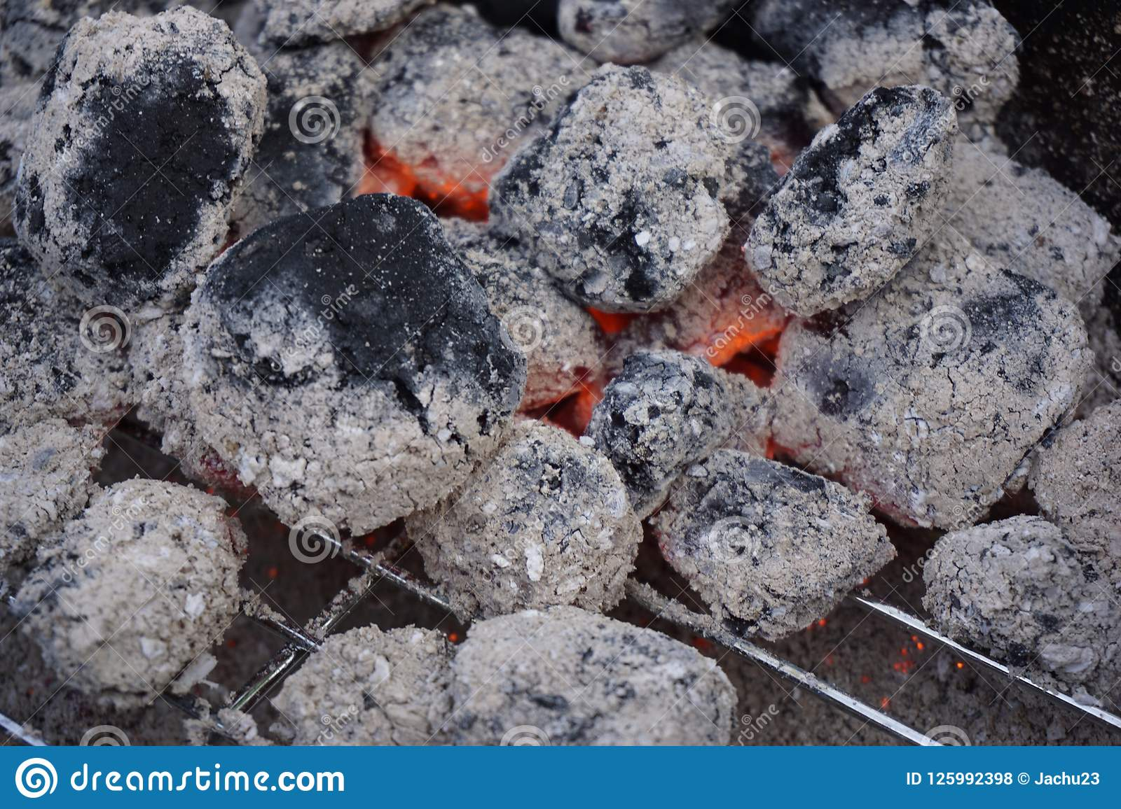 the glowing pieces of charcoal lie on the grill