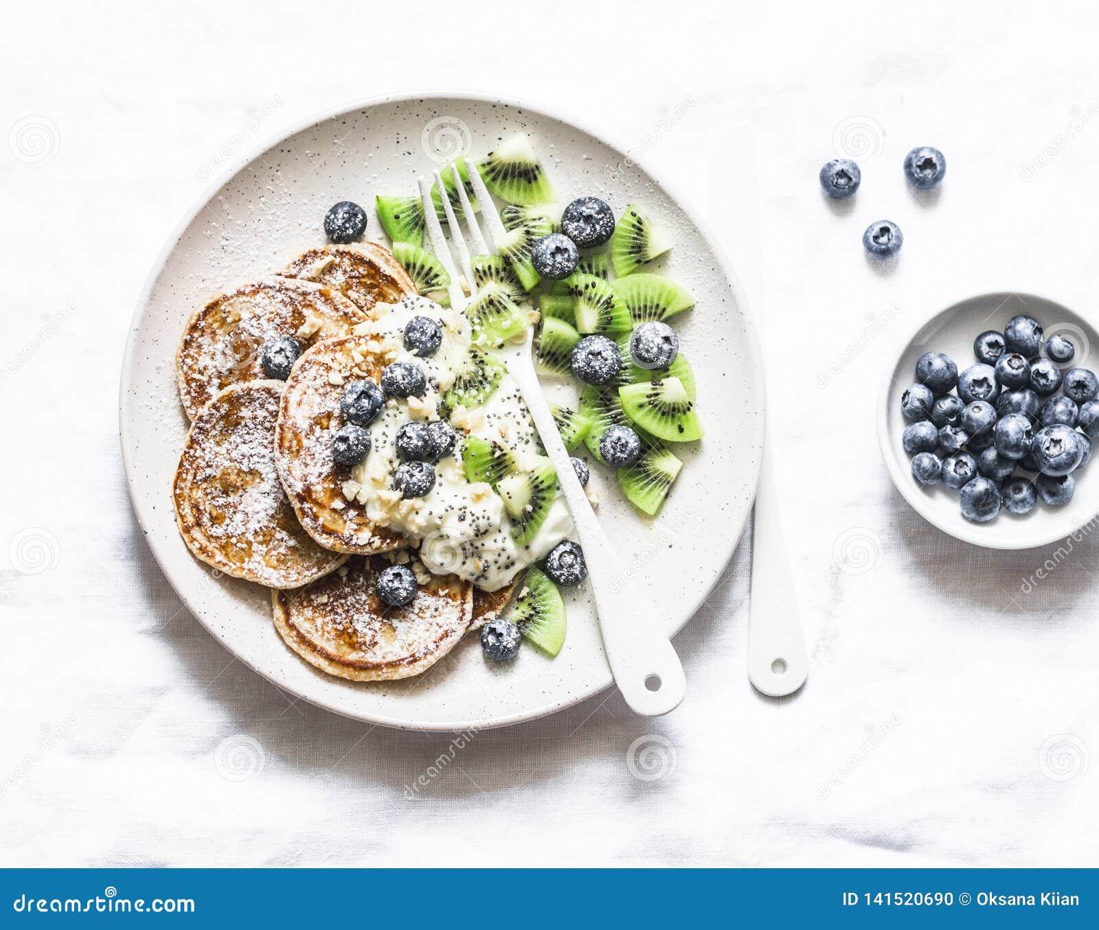 Glutenów bezpłatni bliny z kokosowym jogurtem, kiwi i czarnymi jagodami na lekkim tle,