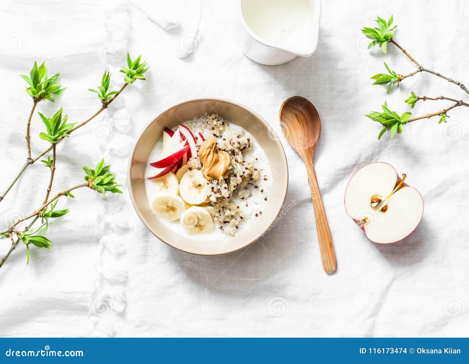 Gluten free breakfast - quinoa, coconut milk, banana, apple, peanut butter bowl on light background, top view. Delicious diet, veg