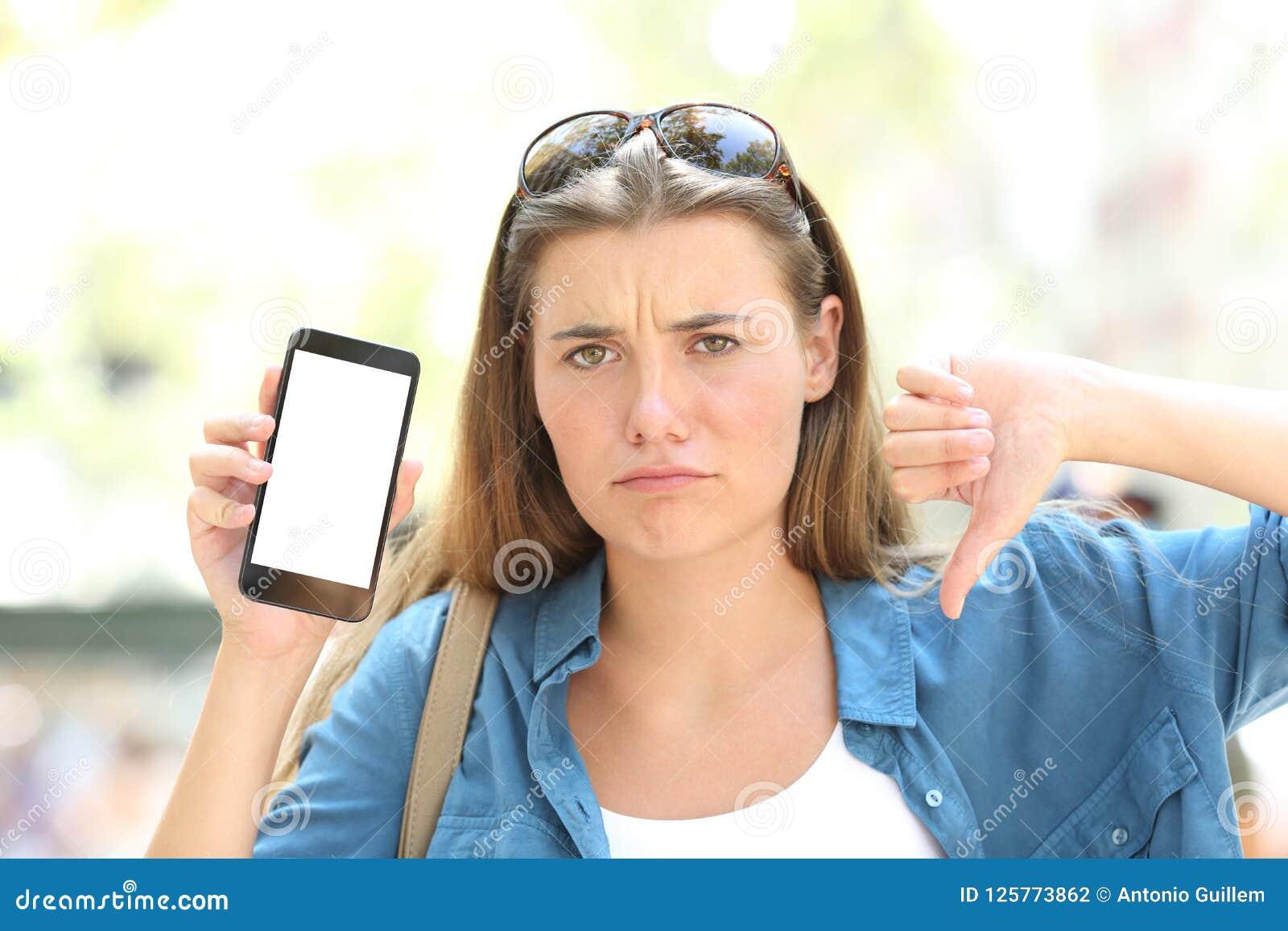 Gniewna dziewczyna pokazuje pustego telefonu ekran z kciuka puszkiem