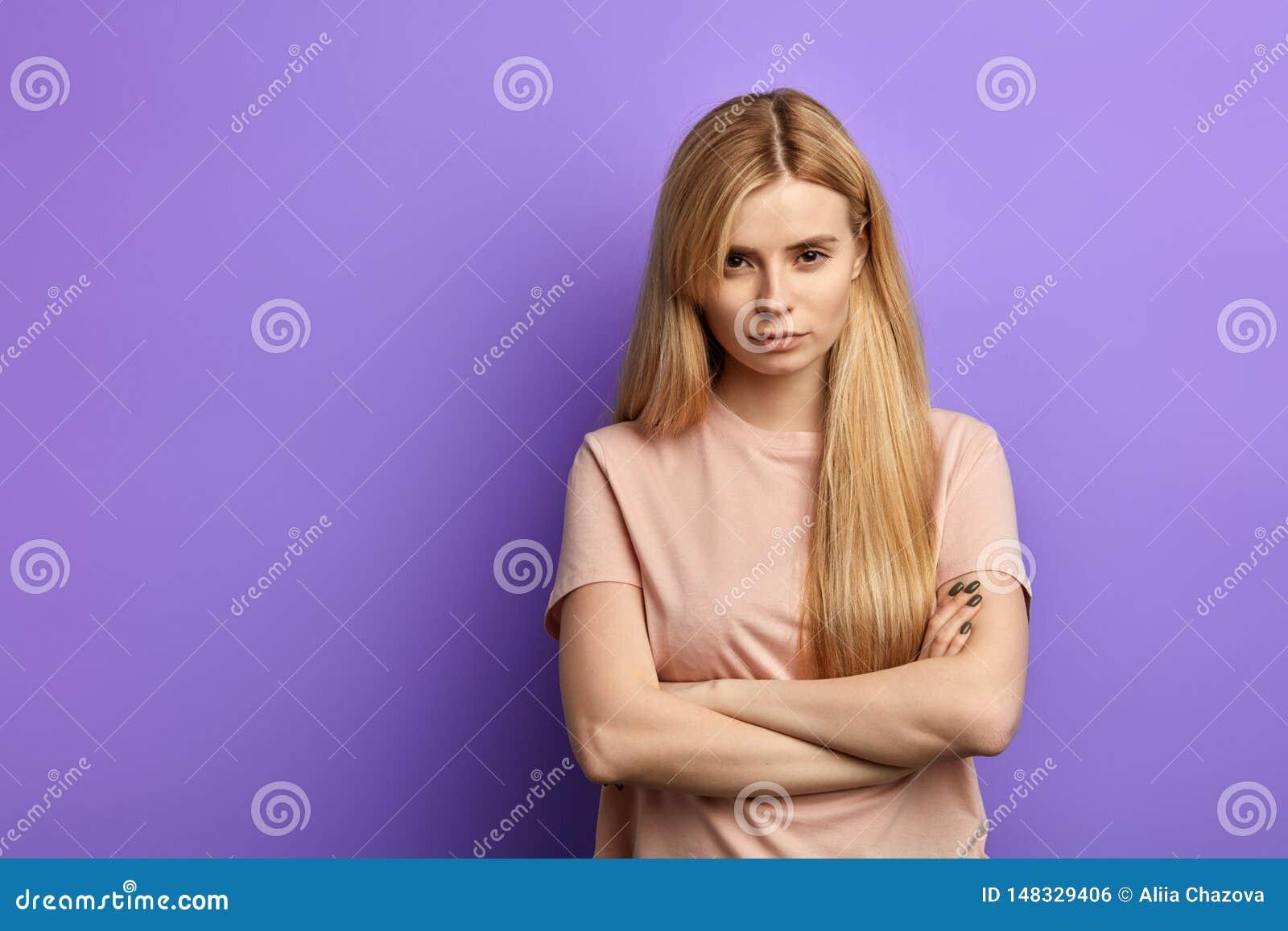 Gniewna gderliwa blondynki m?oda kobieta utrzymuje r?ki sk?ada? w be?owej koszulce
