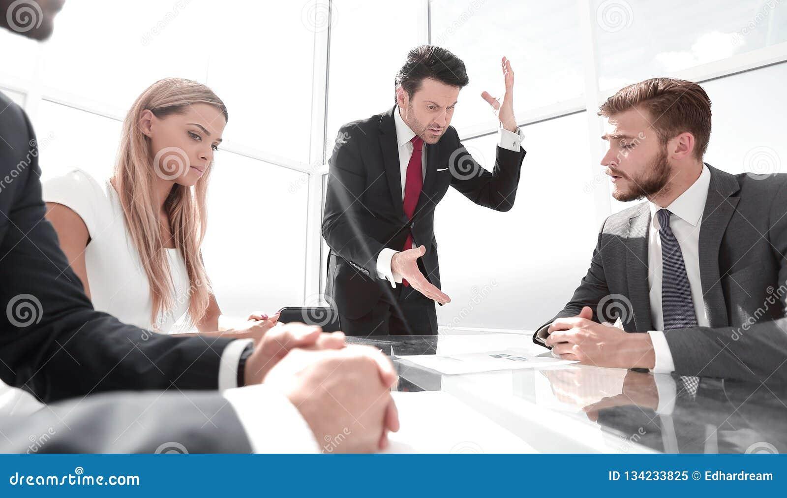 Gniewny biznesmen przy pracującym spotkaniem z biznesową drużyną