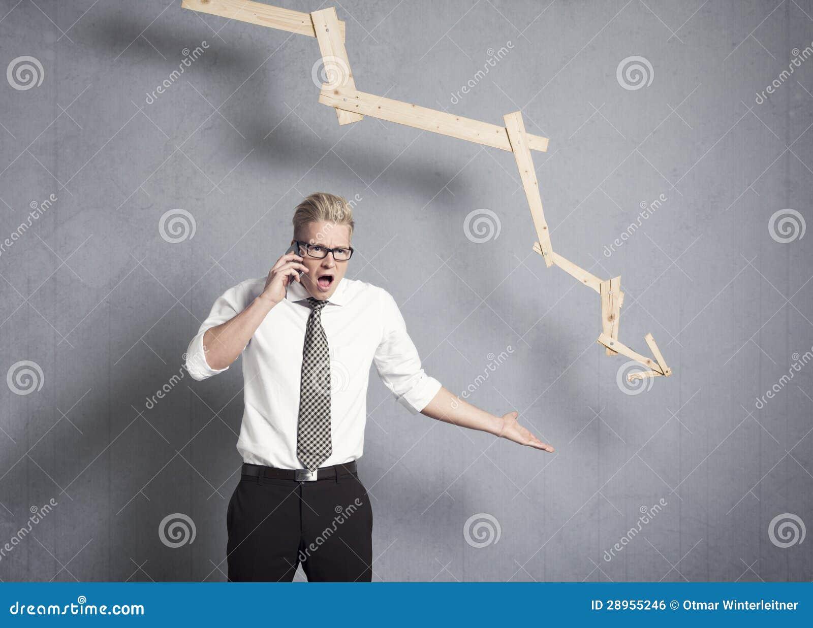 Gniewny biznesmen wskazuje w dół przed wykresem.