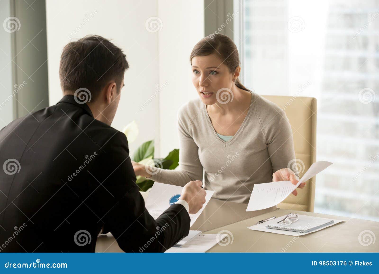 Gniewny bizneswomanu argumentowanie z biznesmenem o papierkowej roboty faja