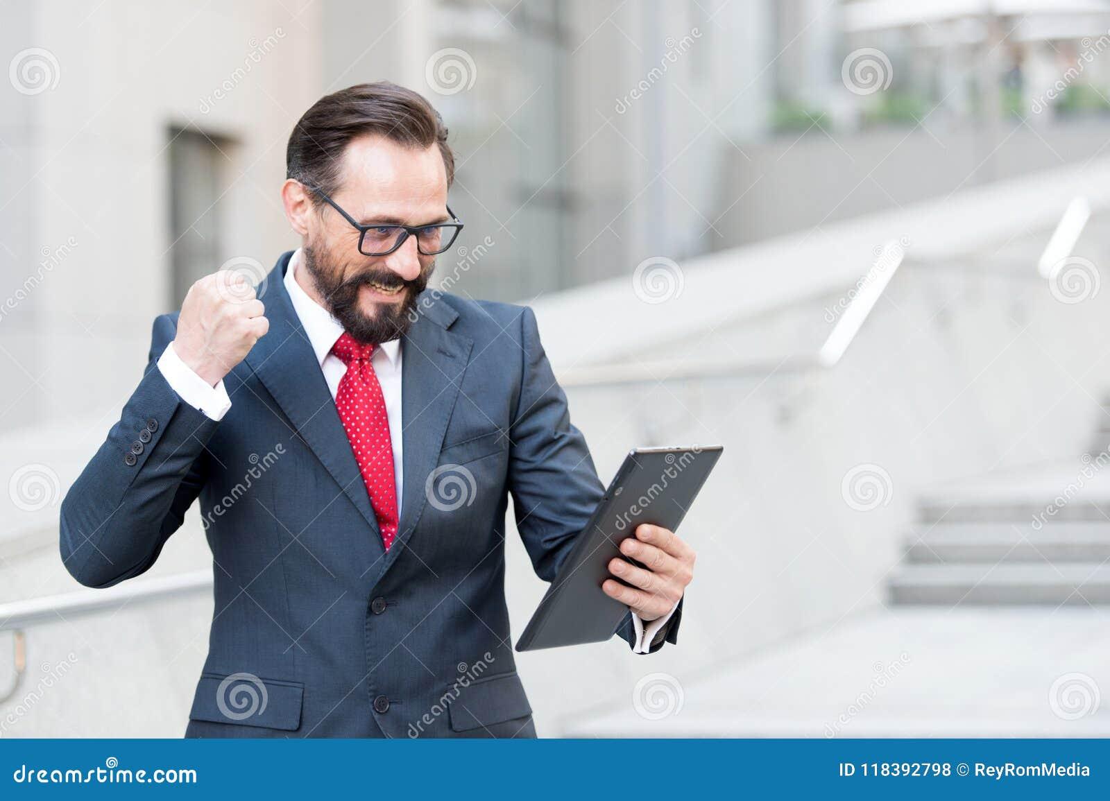 Gniewny brodaty biznesmen ubierał w błękitnym kostiumu grożeniu z pięścią pastylka podczas wideokonferencja z biura