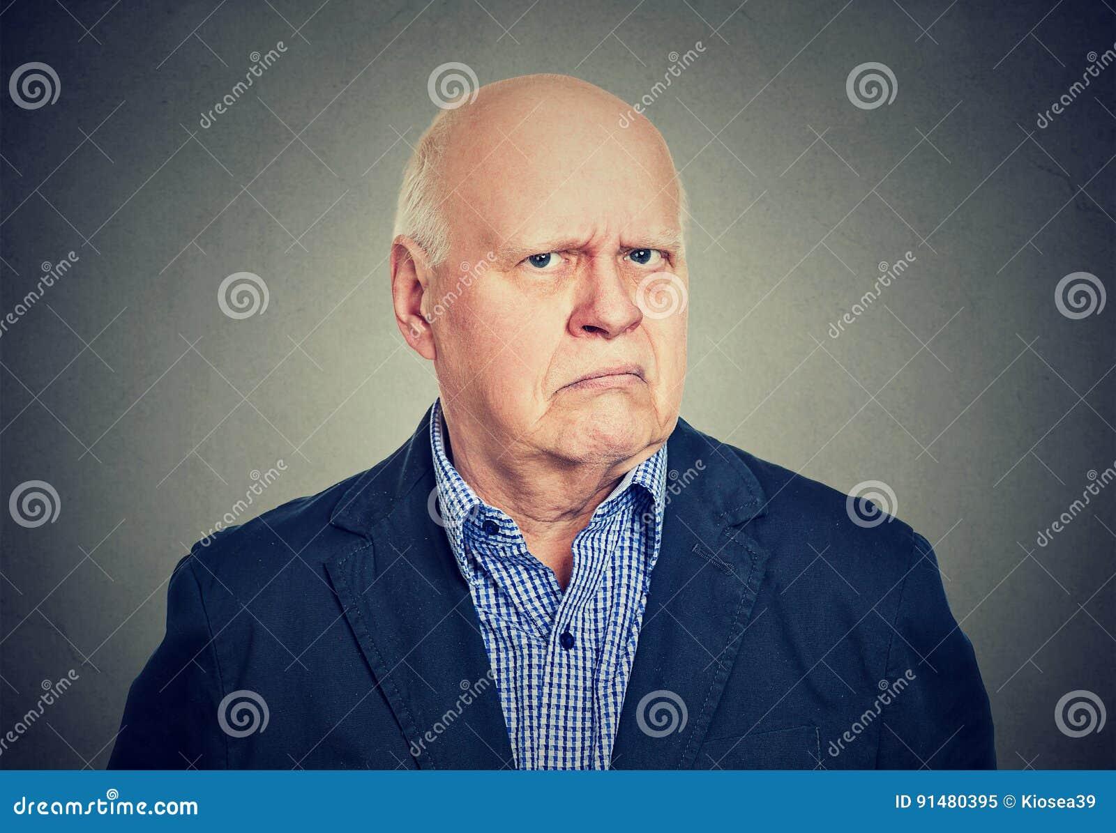 Gniewny, gderliwy starszy biznesowy mężczyzna, odizolowywający na szarym tle