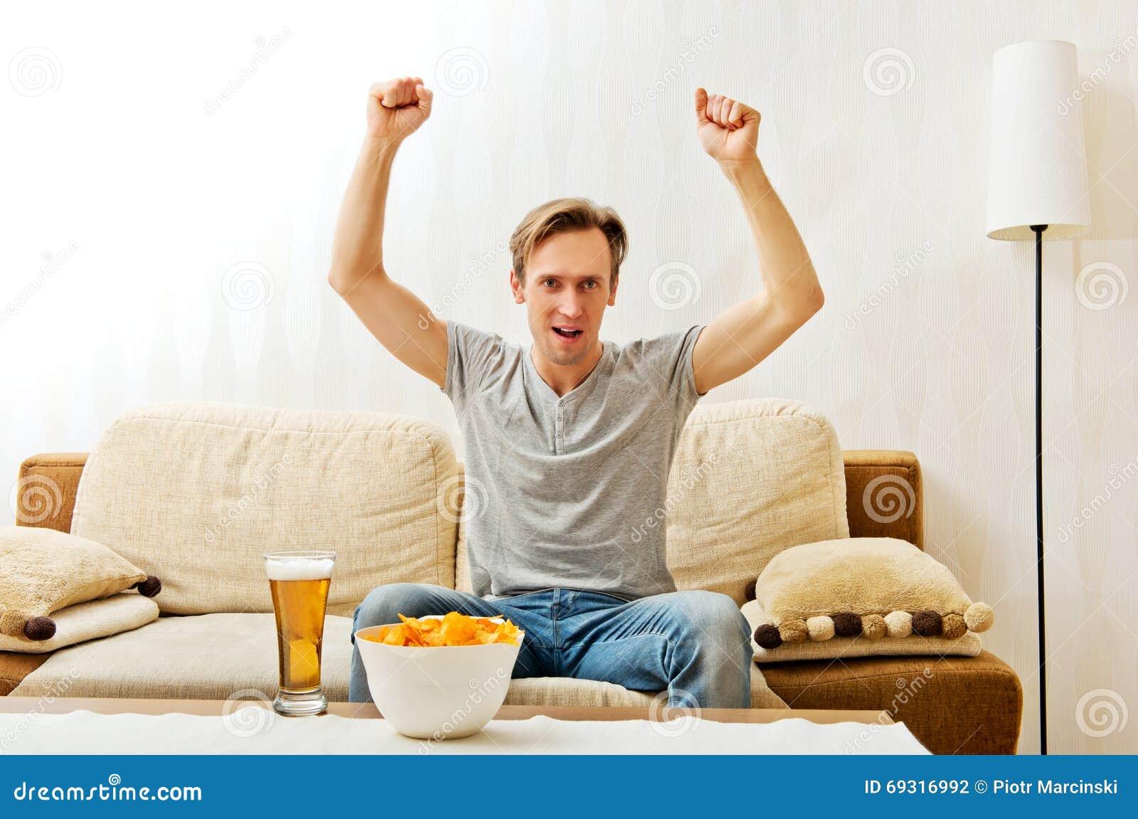 Gniewny mężczyzna krzyczy podczas gdy oglądać bawi się na tv