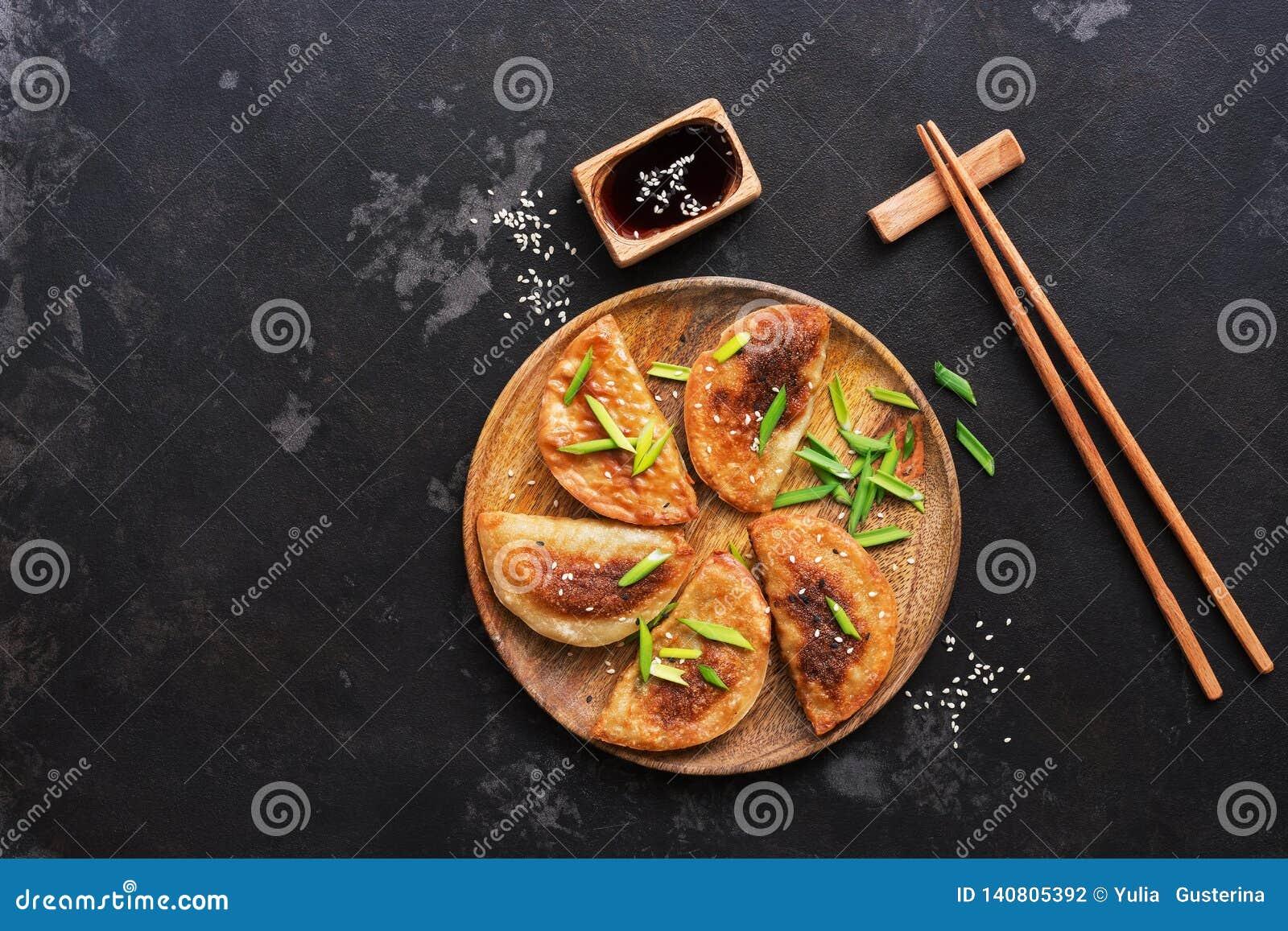 Gnocchi fritti asiatici casalinghi con la erba cipollina, la salsa di soia ed i bastoncini su un fondo di pietra nero Alimento gi