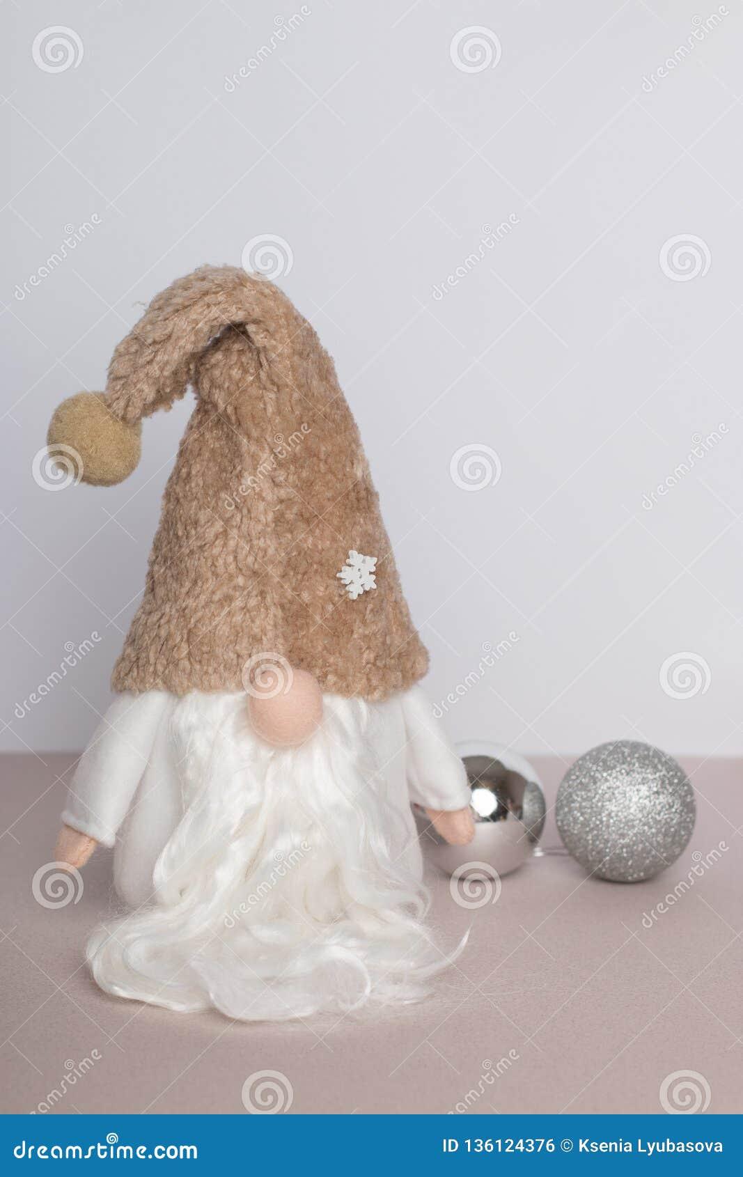 Gnomo escandinavo na roupa branca e no chapéu bege com as bolas de prata de ano novo em um fundo bege