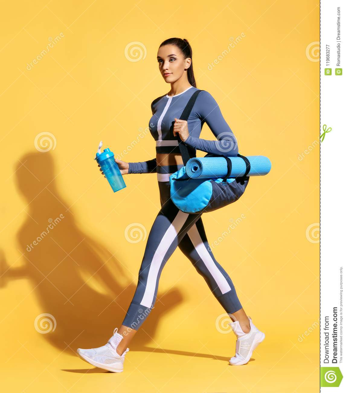 Attractive latin woman in fashionable sportswear on yellow background.