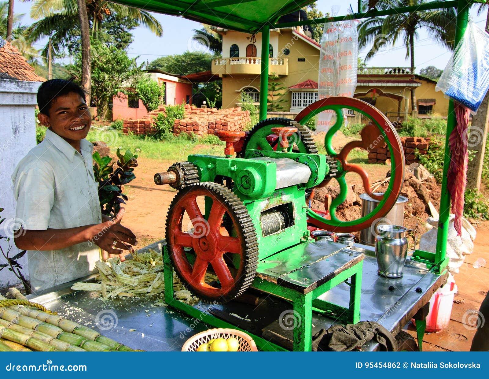 Goa, Índia - 16 de novembro de 2014: Homem novo que cozinha e que vende o suco popular do junco da rua do ` s da Índia