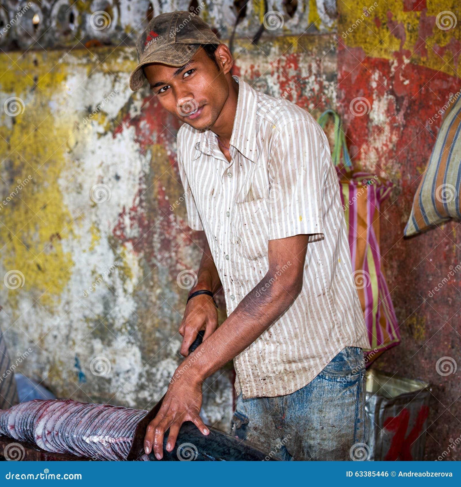 Goa Indien - Februari 2008 - ung man som skivar en stor ny fisk på den berömda veckoMapusa marknaden