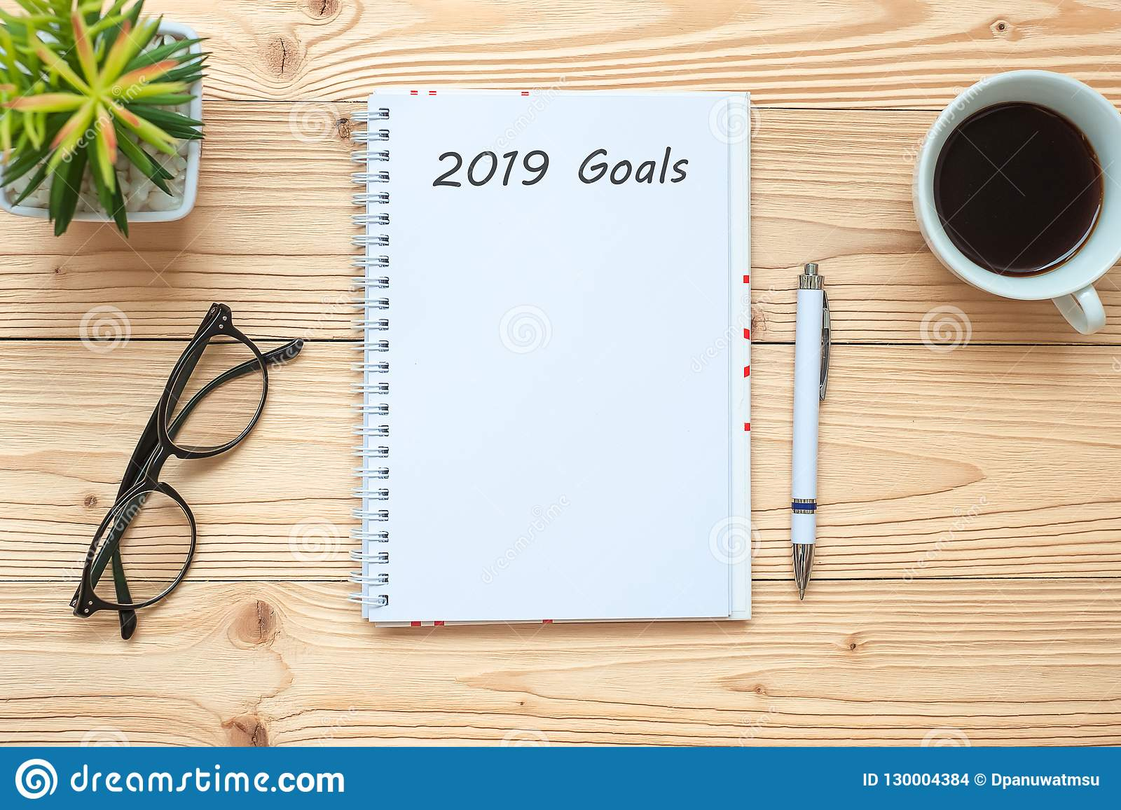 2019 Goals with notebook, black coffee cup, pen and glasses on table, Top view and copy space. New Year New Start, Resolution, Sol