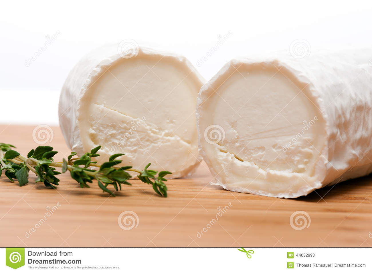 Goat cheese with thyme on a wooden cutting board