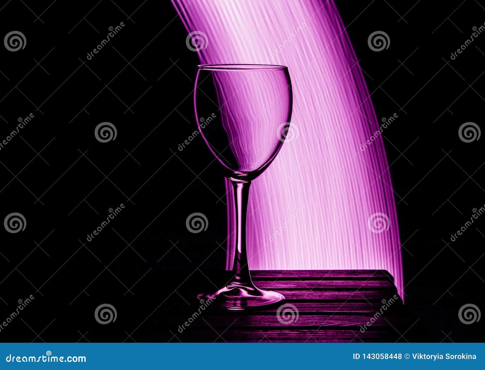 Gobelet en verre sur un fond et un pourpre noirs éclairés à contre-jour