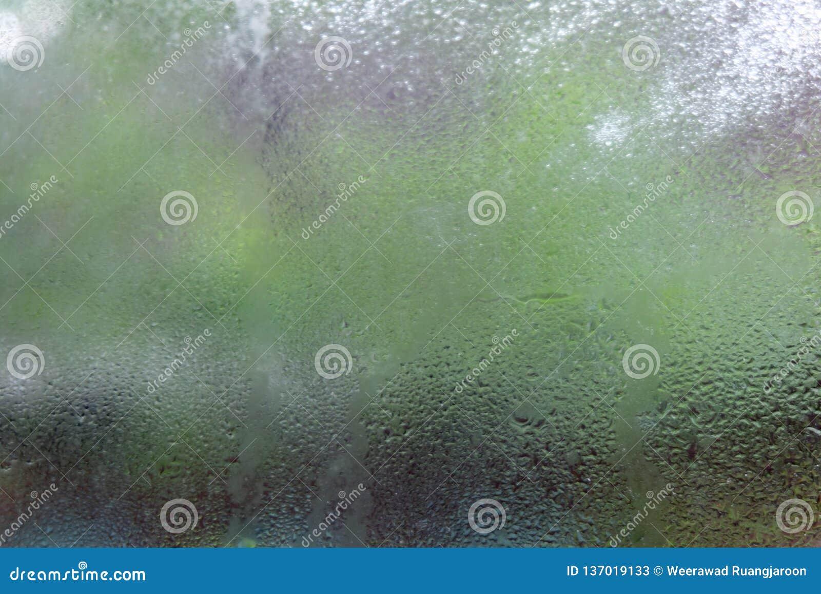 Gocce di acqua o gocciolina della pioggia sul vetro sull vago su con gli ambiti di provenienza