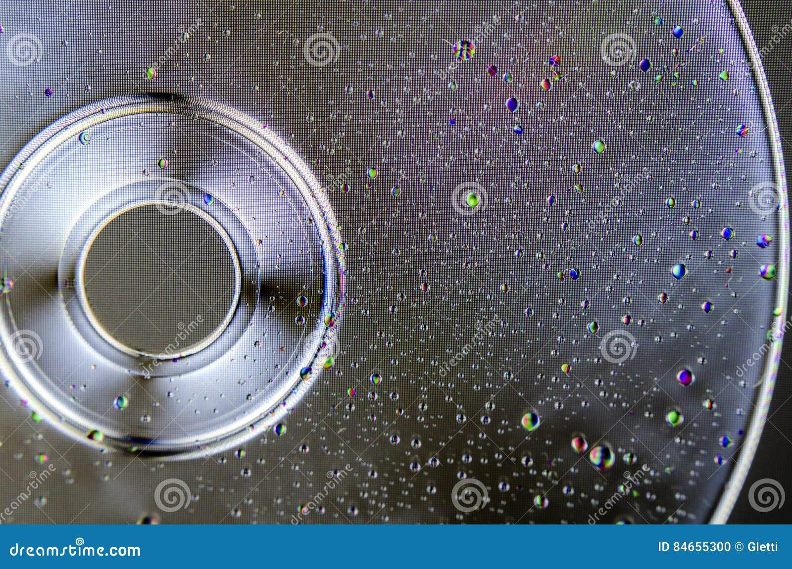Gocce di acqua variopinte sul CD o sul DVD polarizzato