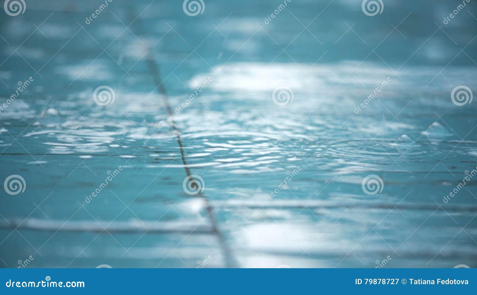 Gocce di pioggia che cadono sulla pavimentazione in piastrelle