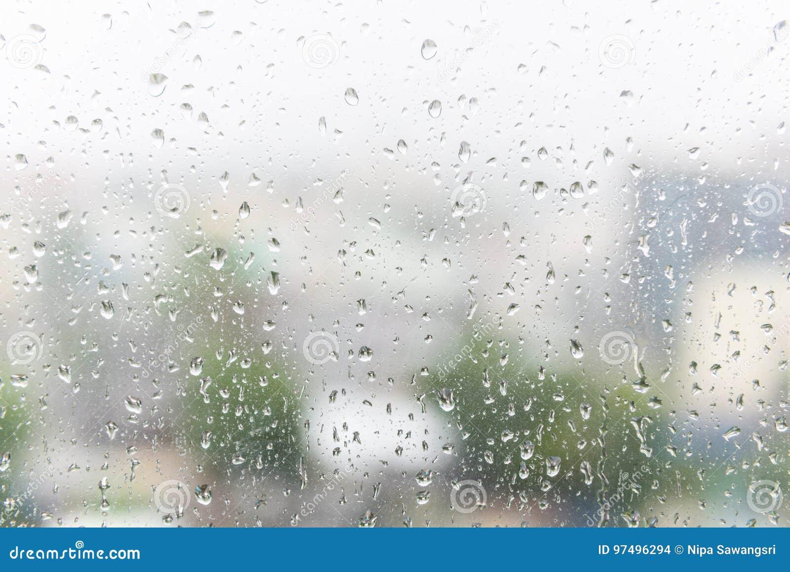 Gocce di pioggia sul vetro di finestra con fondo scuro