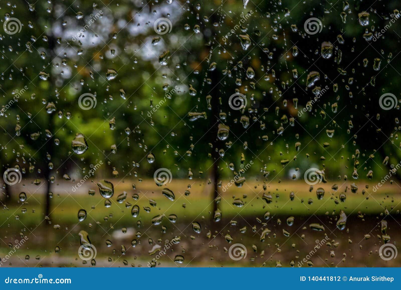 Gocce di pioggia sulla finestra di automobile con luce solare, vetro bagnato, giorno piovoso