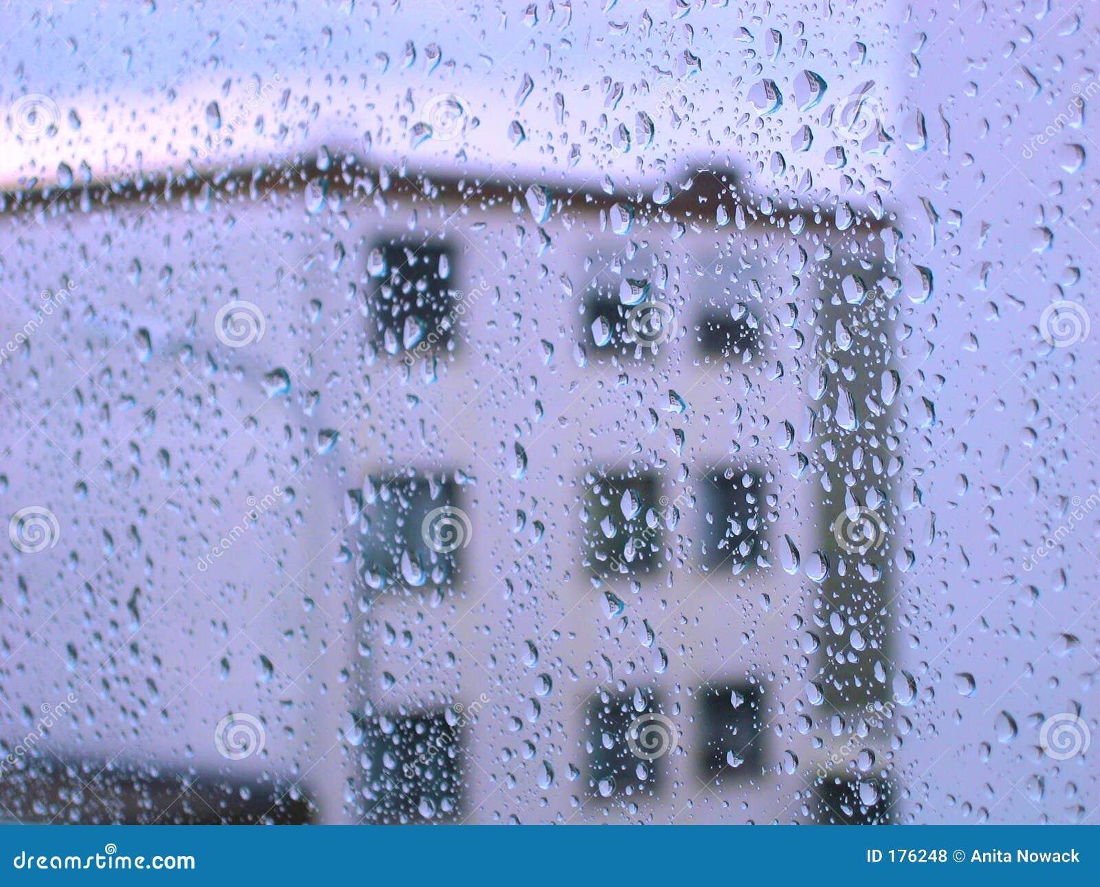 Gocce di pioggia sulla finestra di vetro con la vista della costruzione