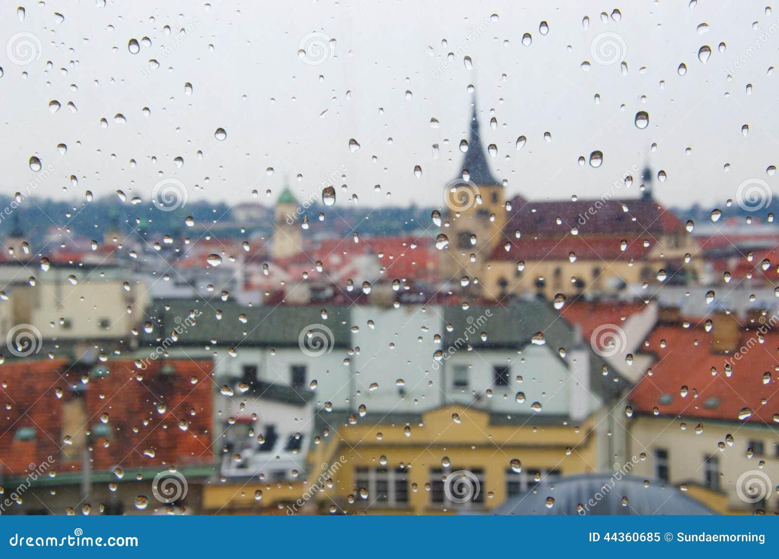 Goccia di acqua alla finestra con il fondo della città